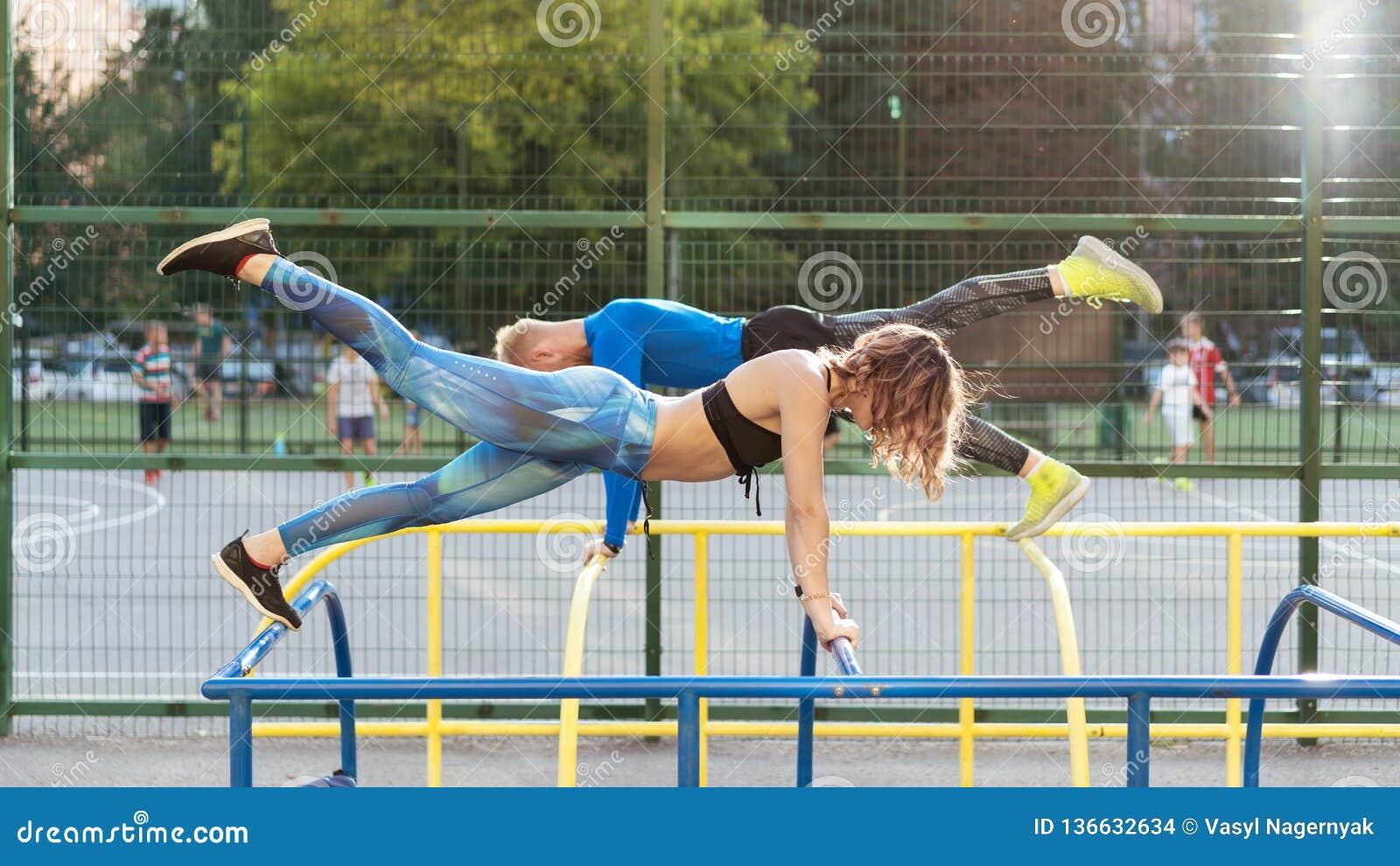 Jonge attrective crossfitman en vrouw die op sportsground uitwerken