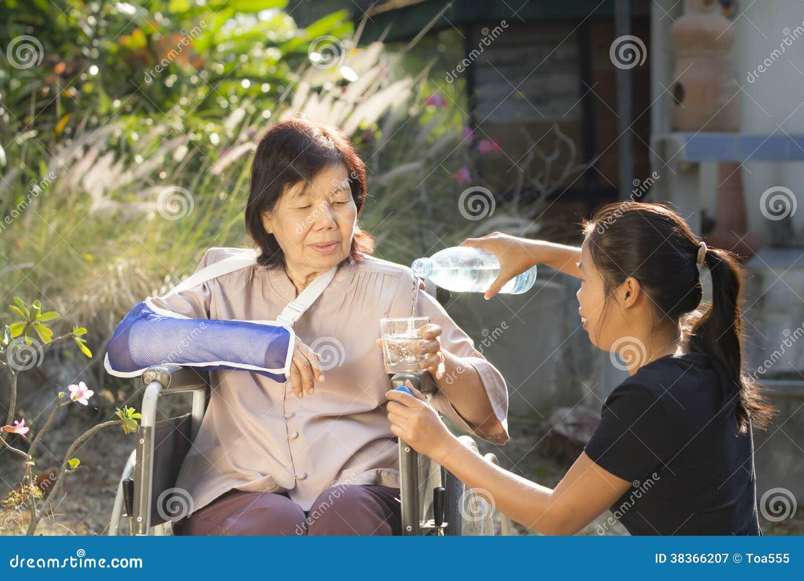 Jonge Aziaat die zorg nemen de hogere vrouw
