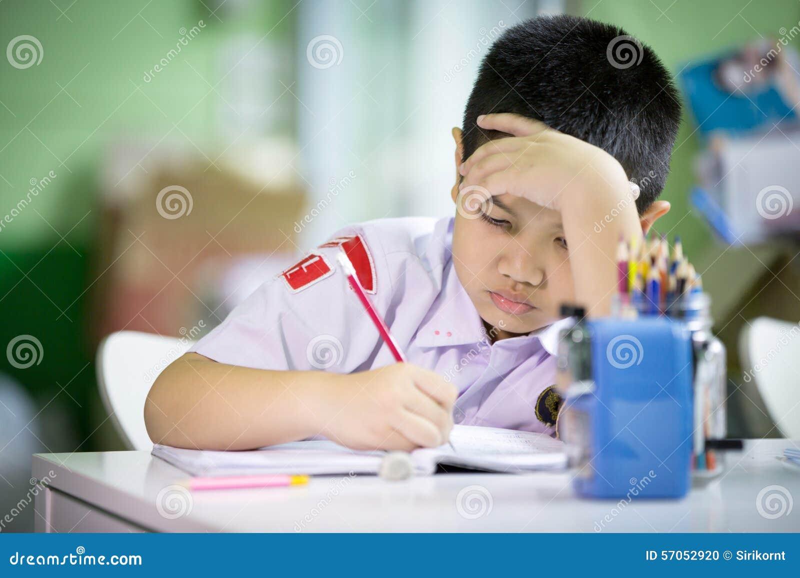 Jonge Aziatische jongen die zijn thuiswerk doen