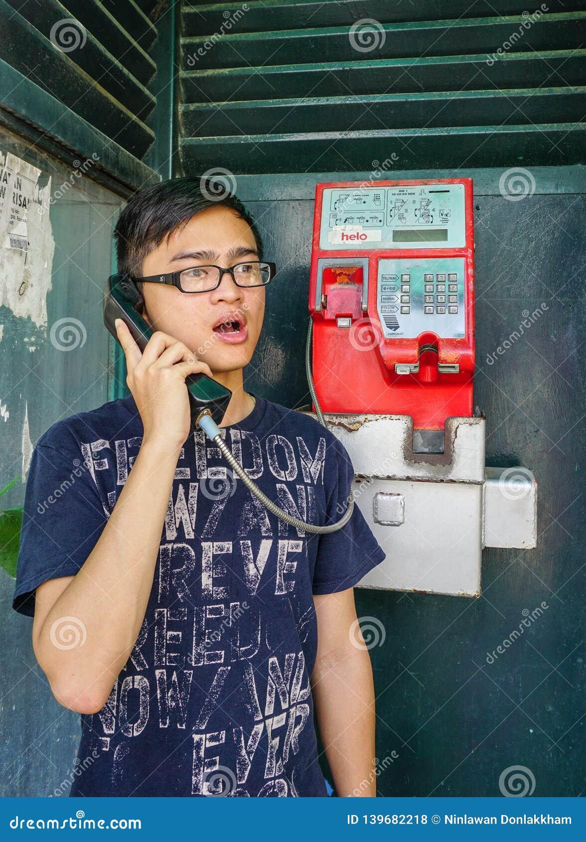 Jonge Aziatische mens die op straattelefoon spreken
