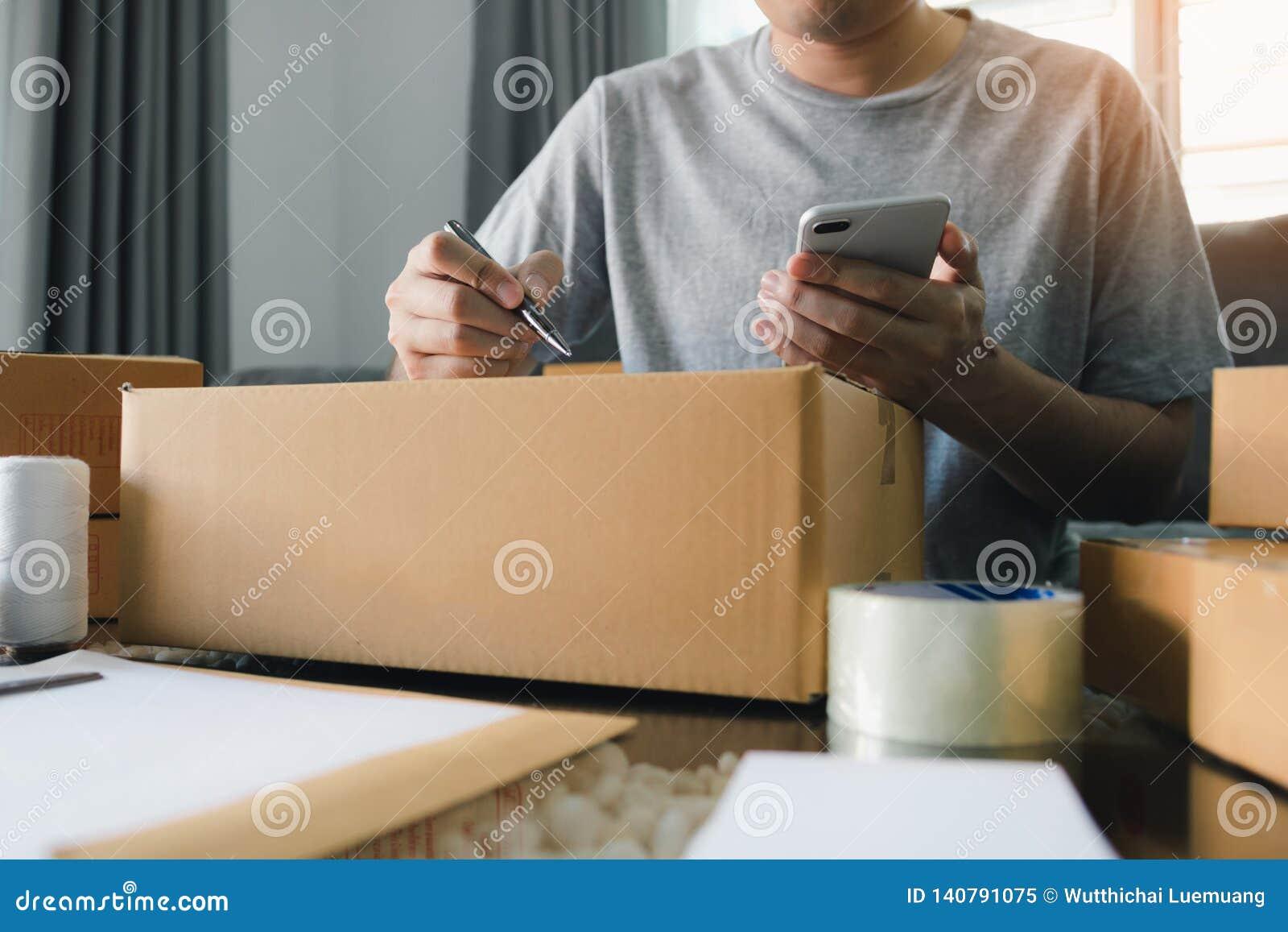 Jonge Aziatische mensen bedrijfseigenaarhanden die adres op kartondoos schrijven op werkplaats of huiskantoor