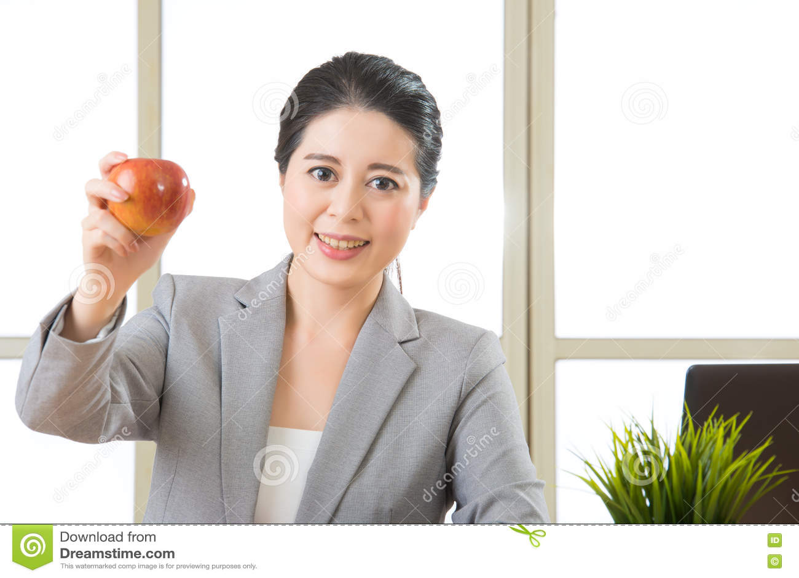 Jonge Aziatische onderneemster die gezonde snack, appel eten