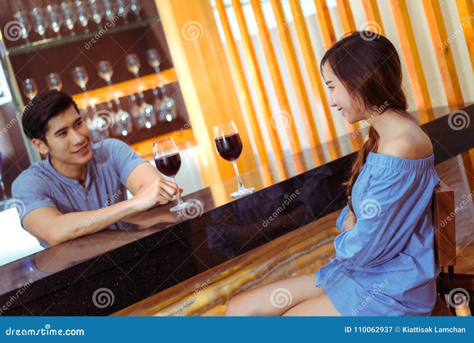 Jonge Aziatische paar samen man en vrouw die met glazen spreken