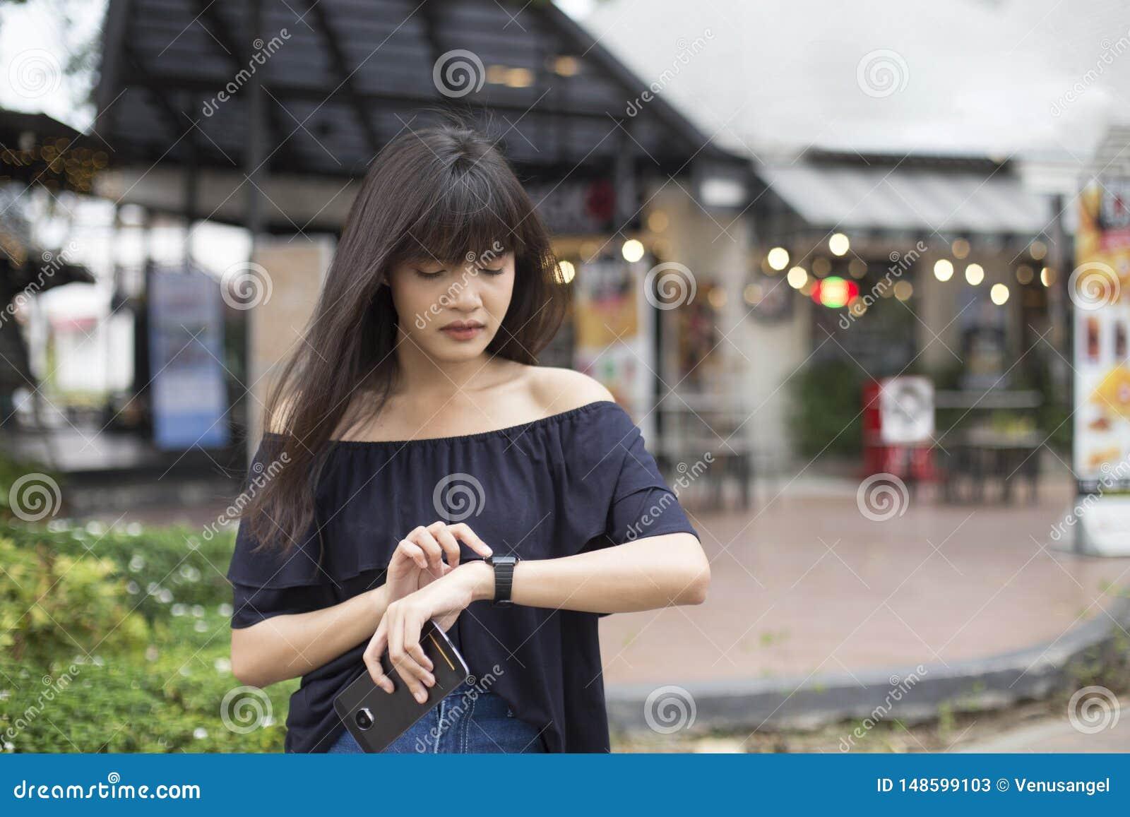 Jonge Aziatische smartphone van de vrouwenholding en het bekijken polshorloge met zorggezicht