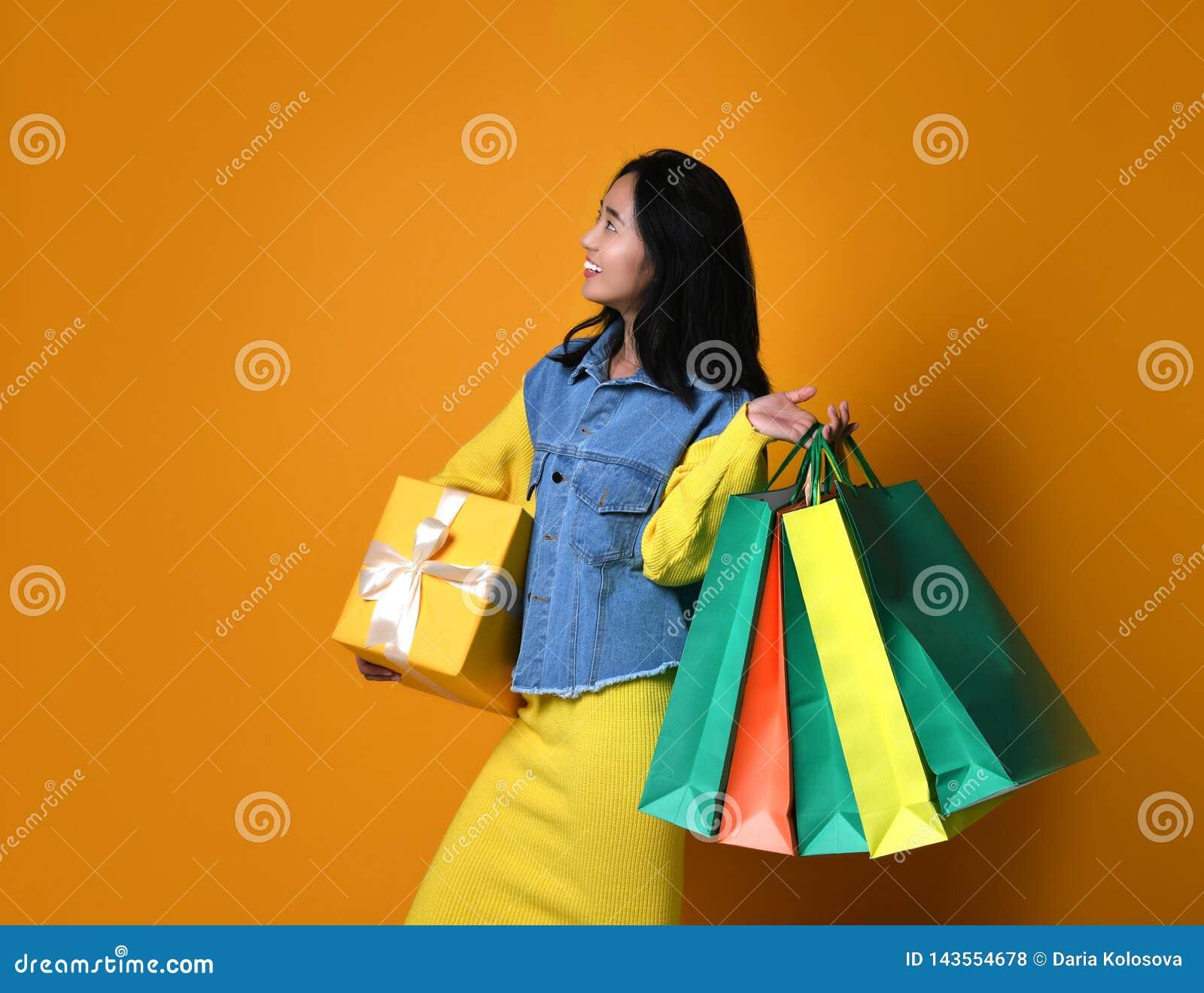 Jonge Aziatische vrouw met het winkelen zakken op kleurenachtergrond