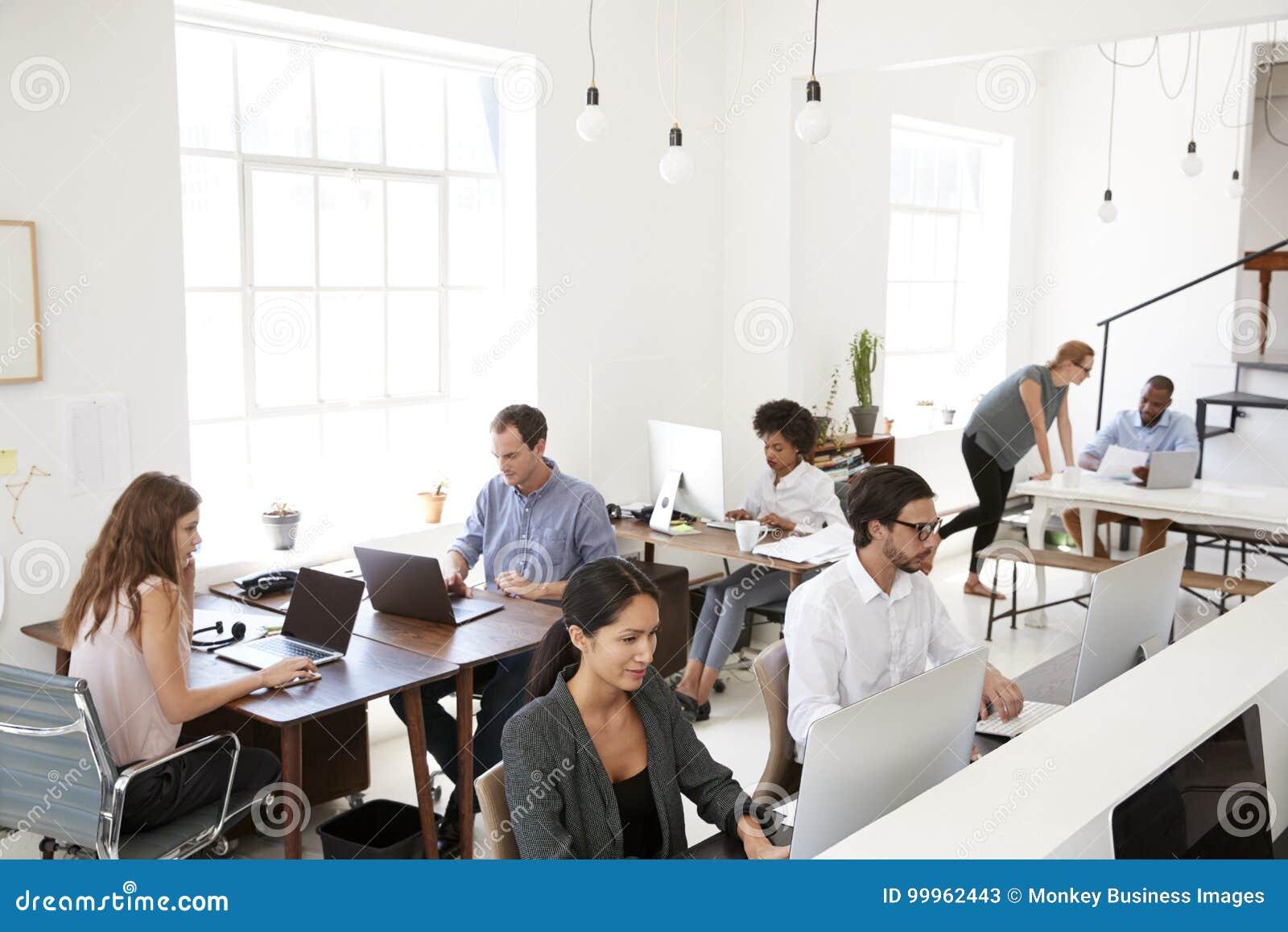 Jonge bedrijfscollega s die bij computers in een bureau werken