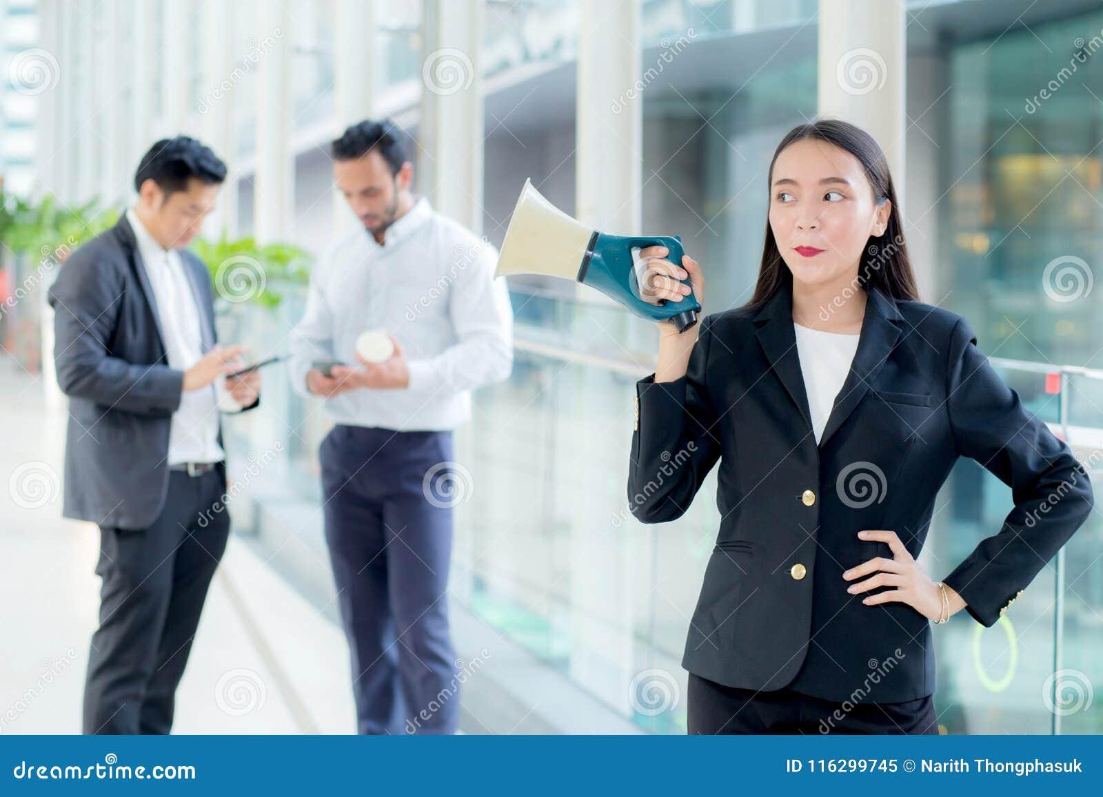 Jonge bedrijfsvrouw die bij de megafoon van de bureauholding werken