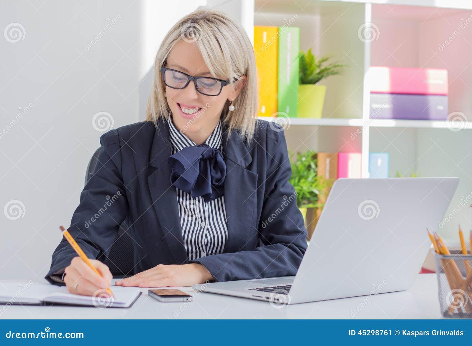 Jonge bedrijfsvrouw die lijst schrijven te doen terwijl het zitten bij haar bureau