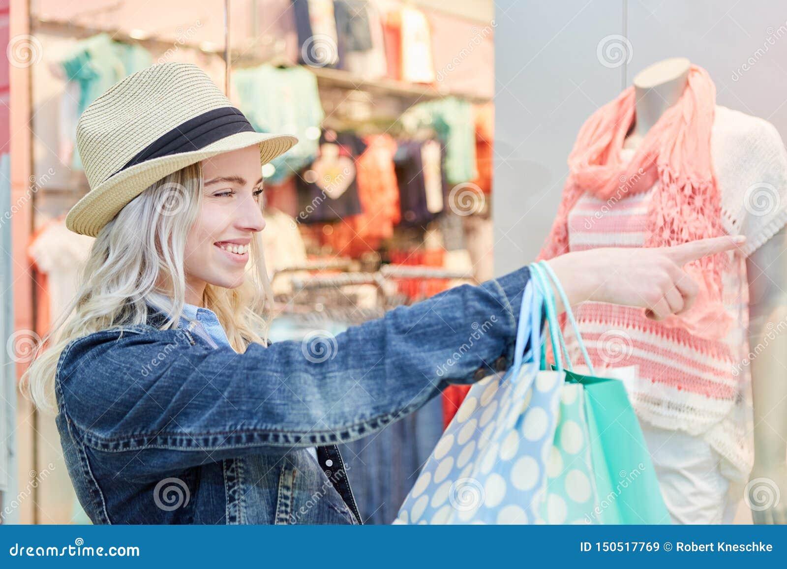 Jonge blonde vrouw voor een boutique