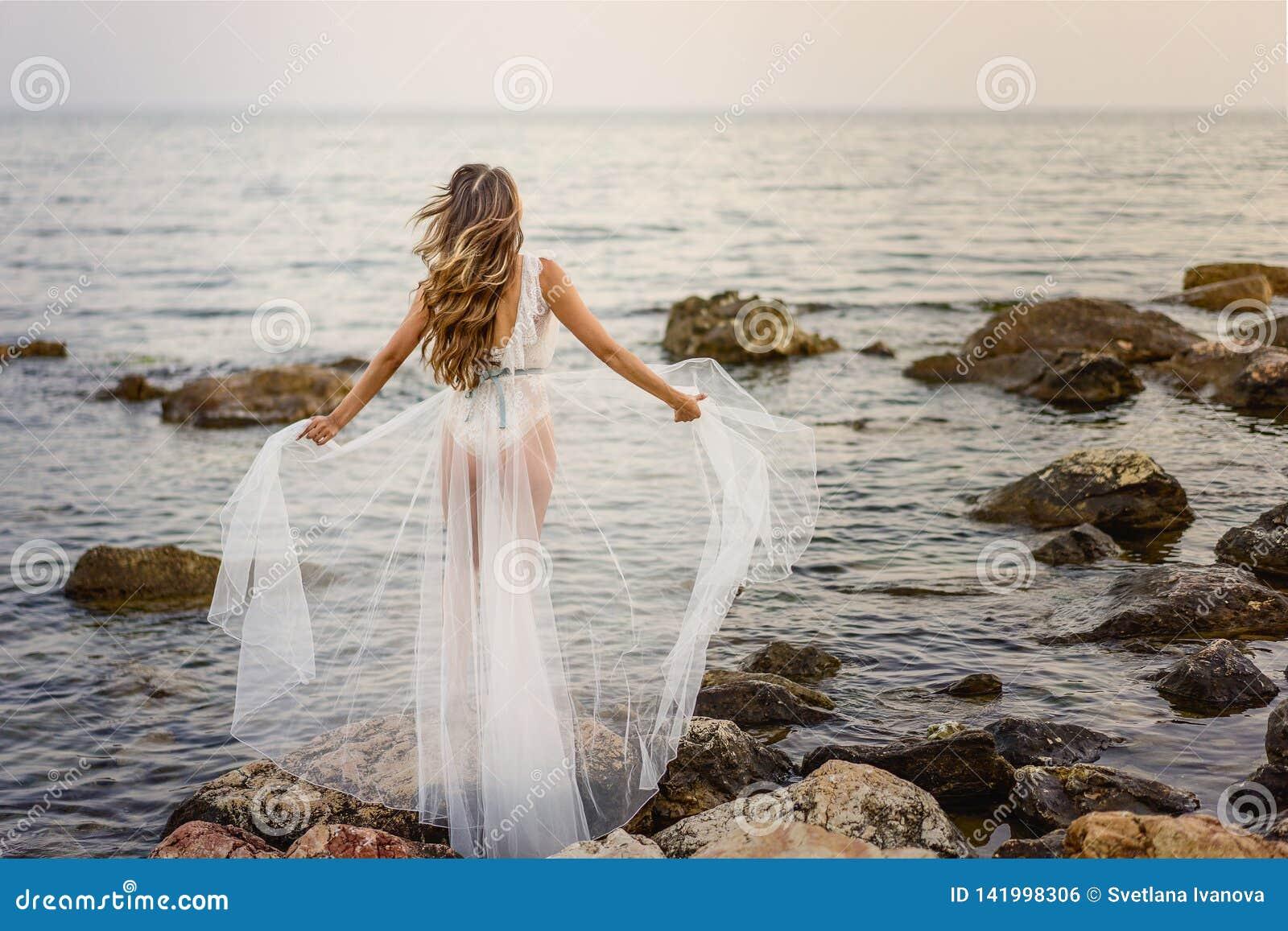 Jonge blonde vrouw in witte de zomerkleding die zich op de rotsen bevindt en het overzees bekijkt Het Kaukasische meisje geniet v