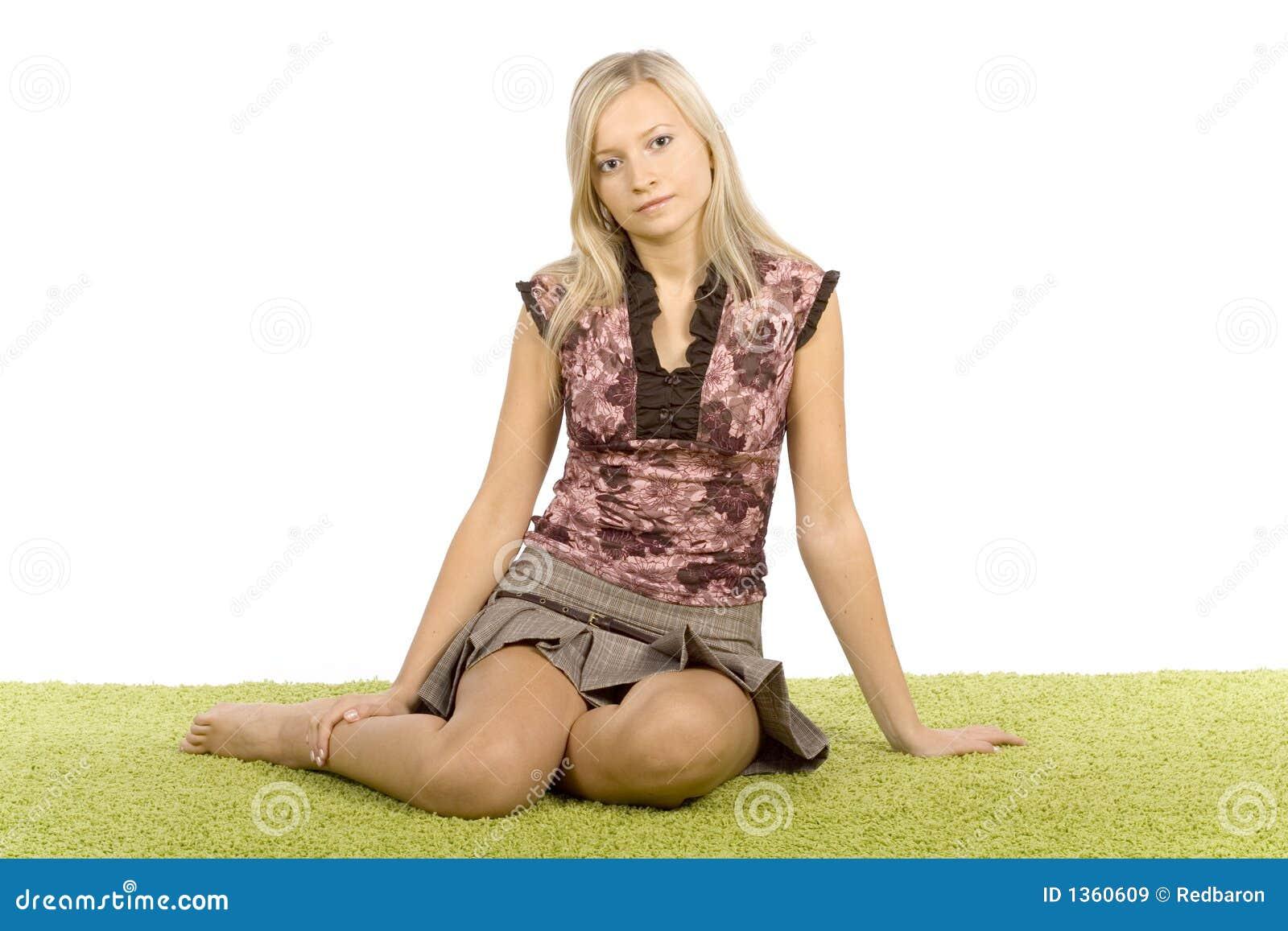 Jonge blonde vrouwenzitting op het groene tapijt