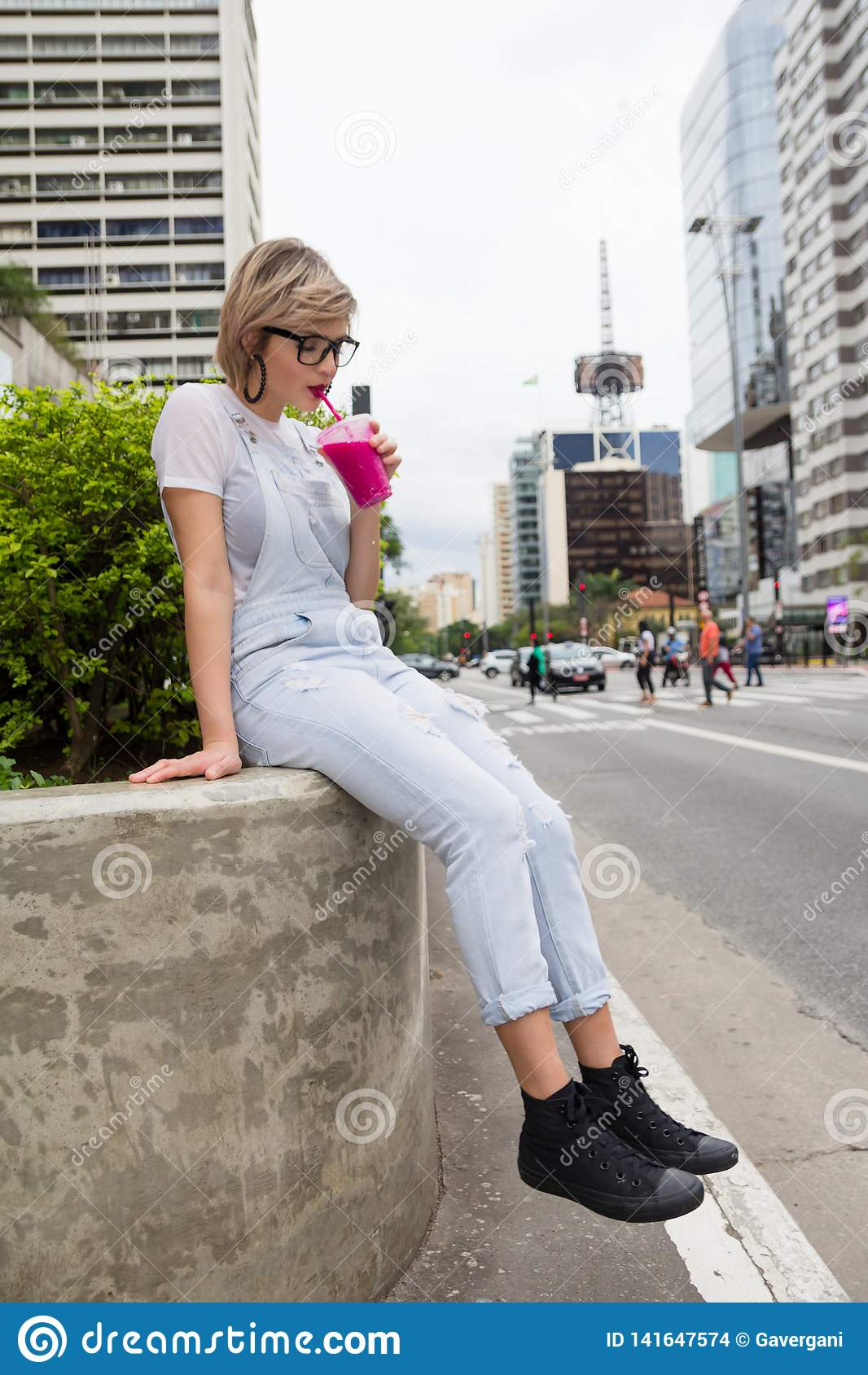 Jonge blondevrouw in de stad die kleurrijke smoothie drinken