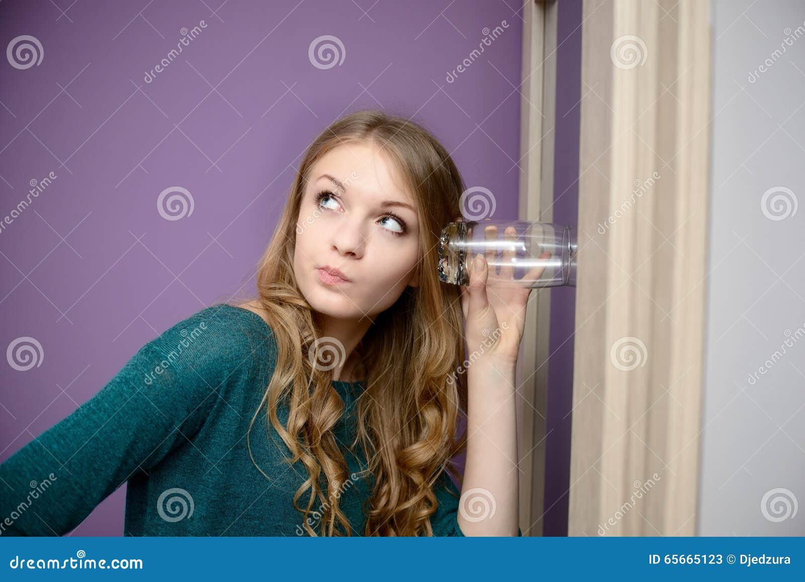 Jonge blondevrouw die binnen aan een gesprek met een glas luisteren
