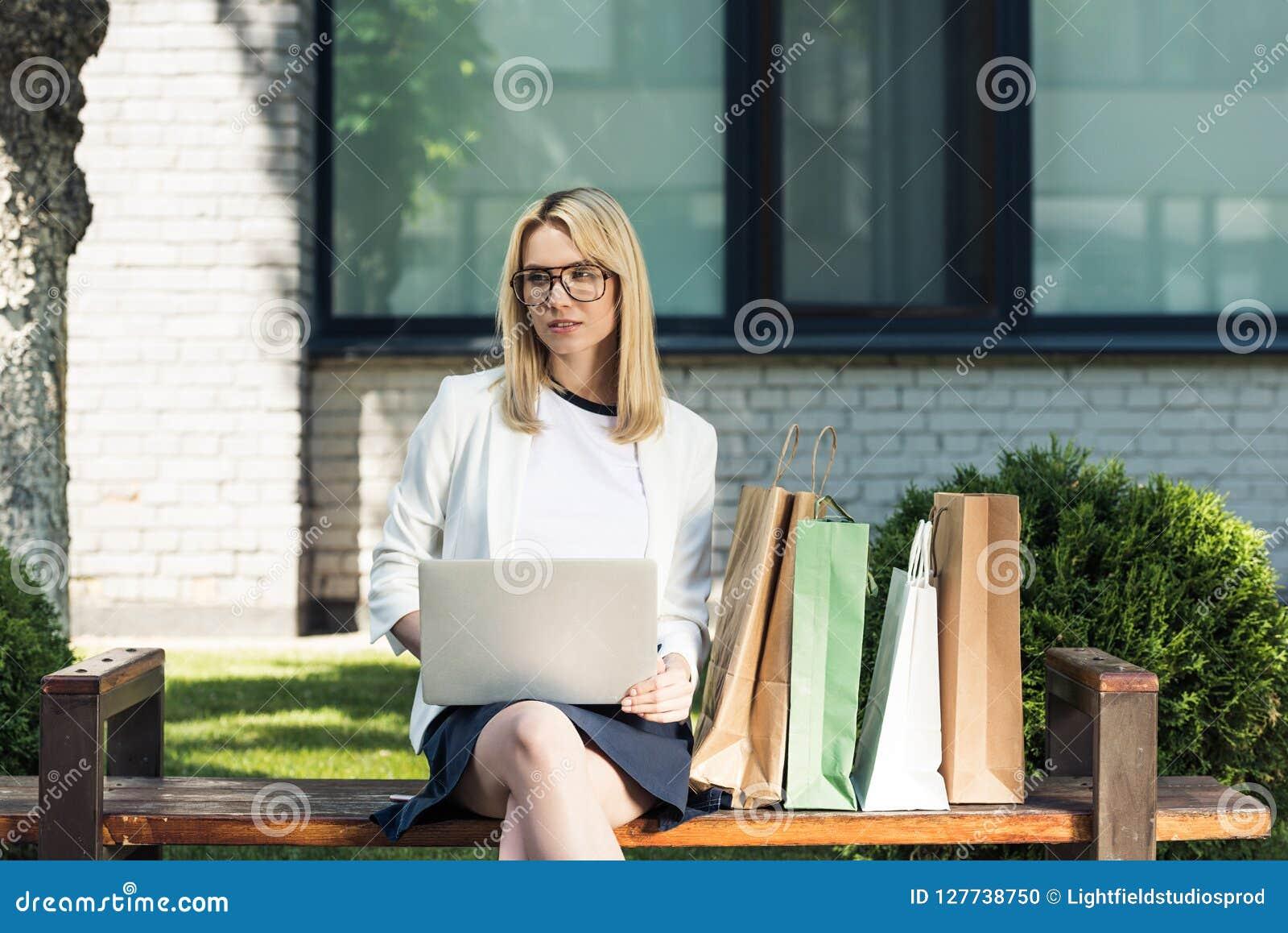 Jonge blondevrouw in oogglazen die laptop met behulp van terwijl het zitten op bank
