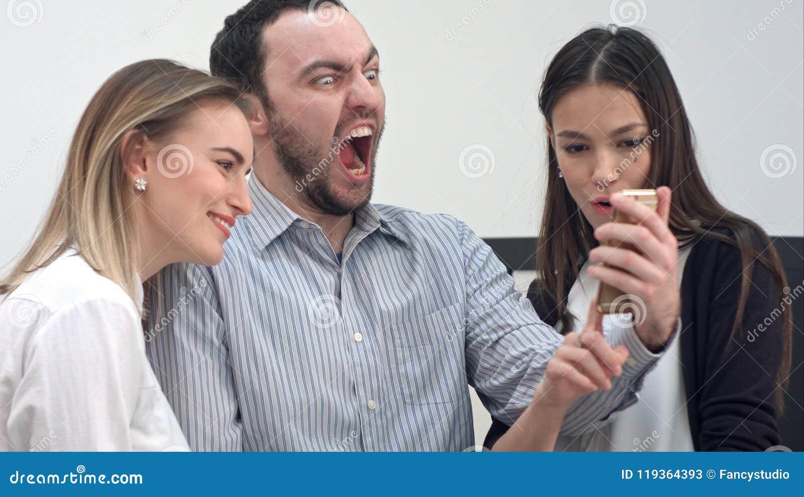 Jonge bureaumedewerkers die pret hebben die selfies op de telefoon nemen