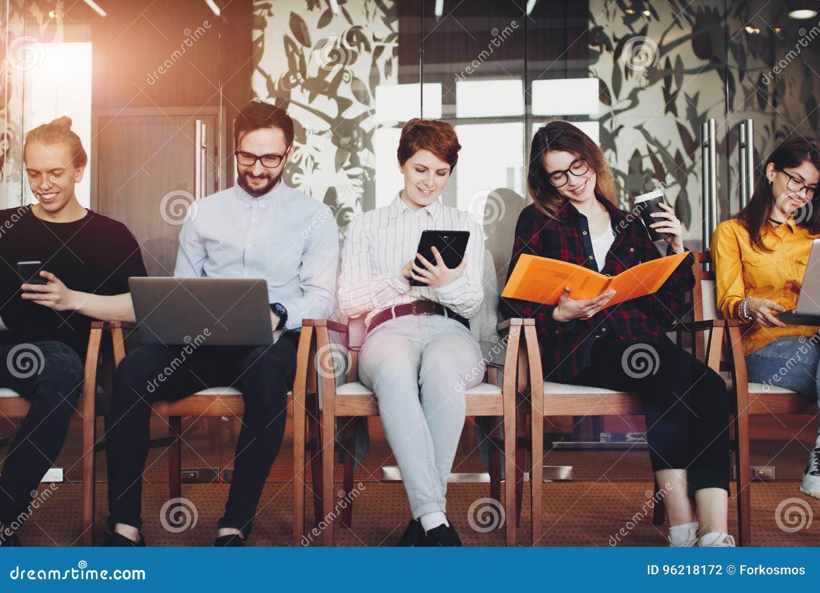 Jonge commerciële bemanning in groot modern zolderbureau Het jonge bureauwerk