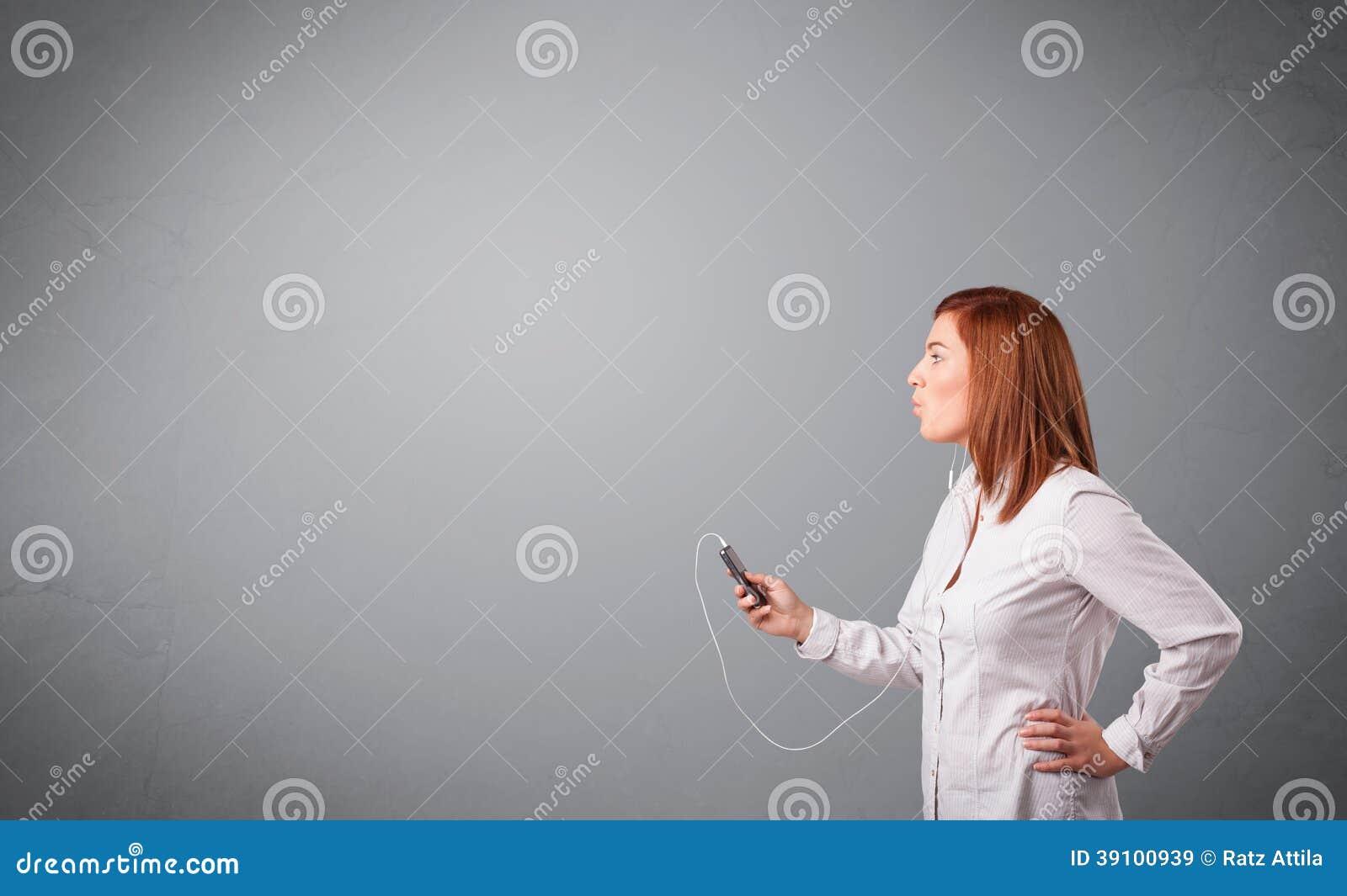 Jonge dame die en aan muziek zingen luisteren