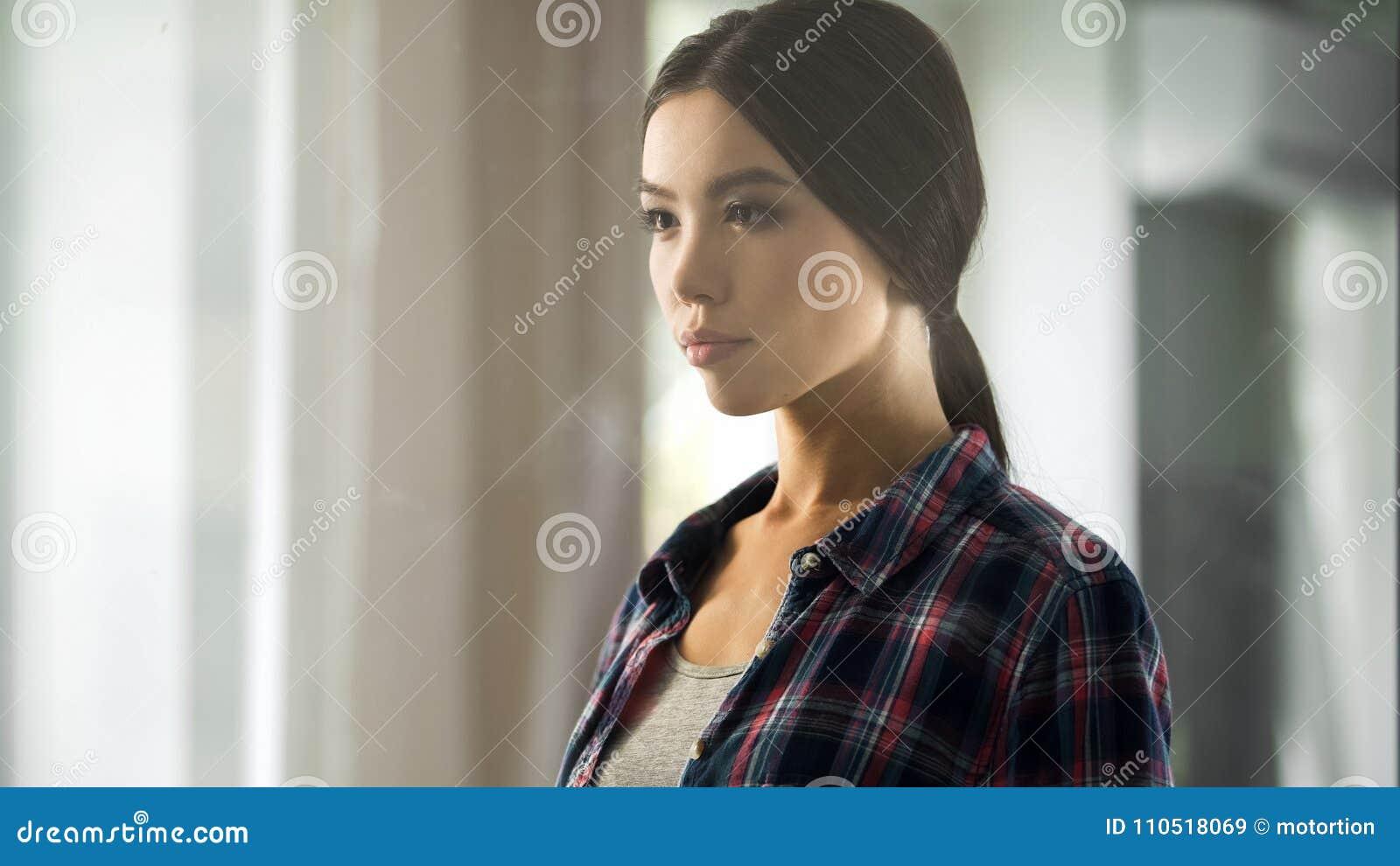 Jonge dame die muurklok, wachtend op vriendvergadering, het denken dagplan kijken