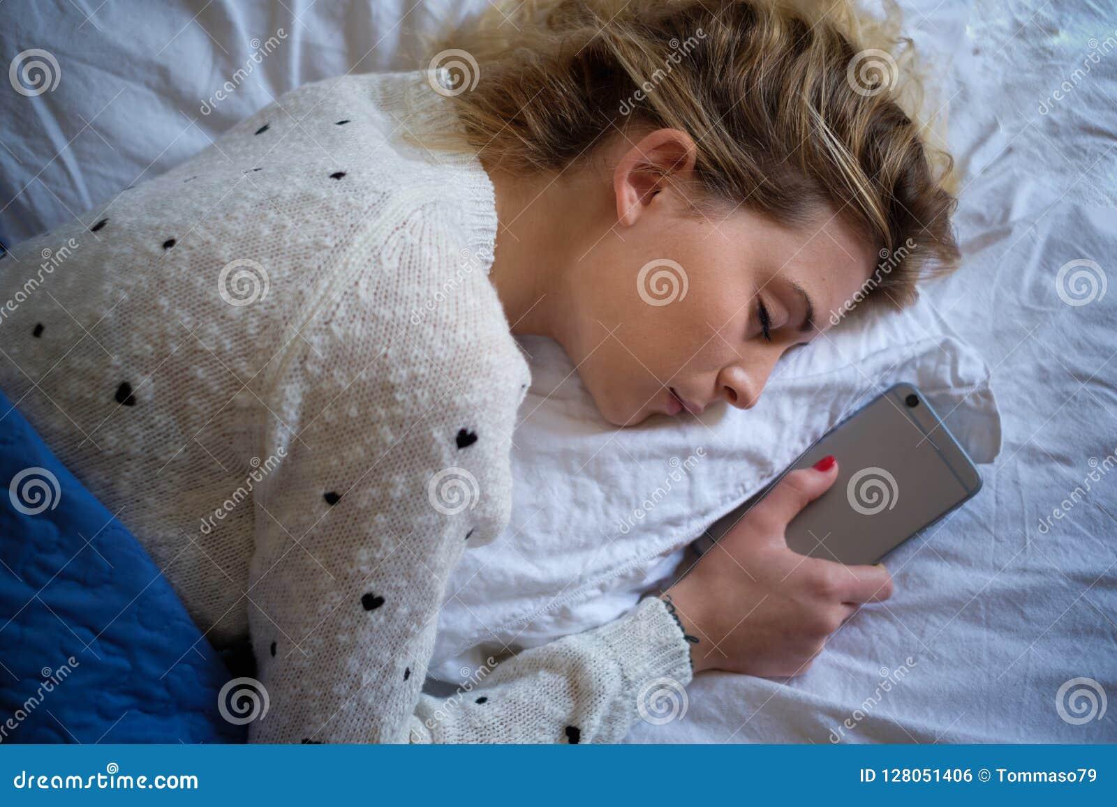 Jonge de slaap en de holdings mobiele telefoon van het tienermeisje