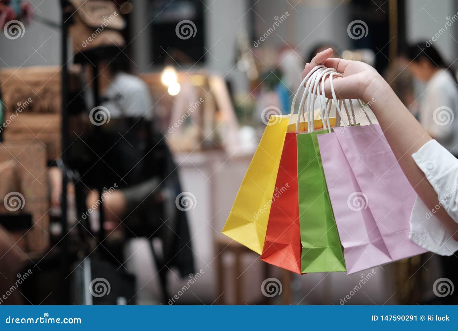 Jonge de verkoop van de vrouwenholding het winkelen zakken het concept van de consumentismelevensstijl in het winkelcomplex