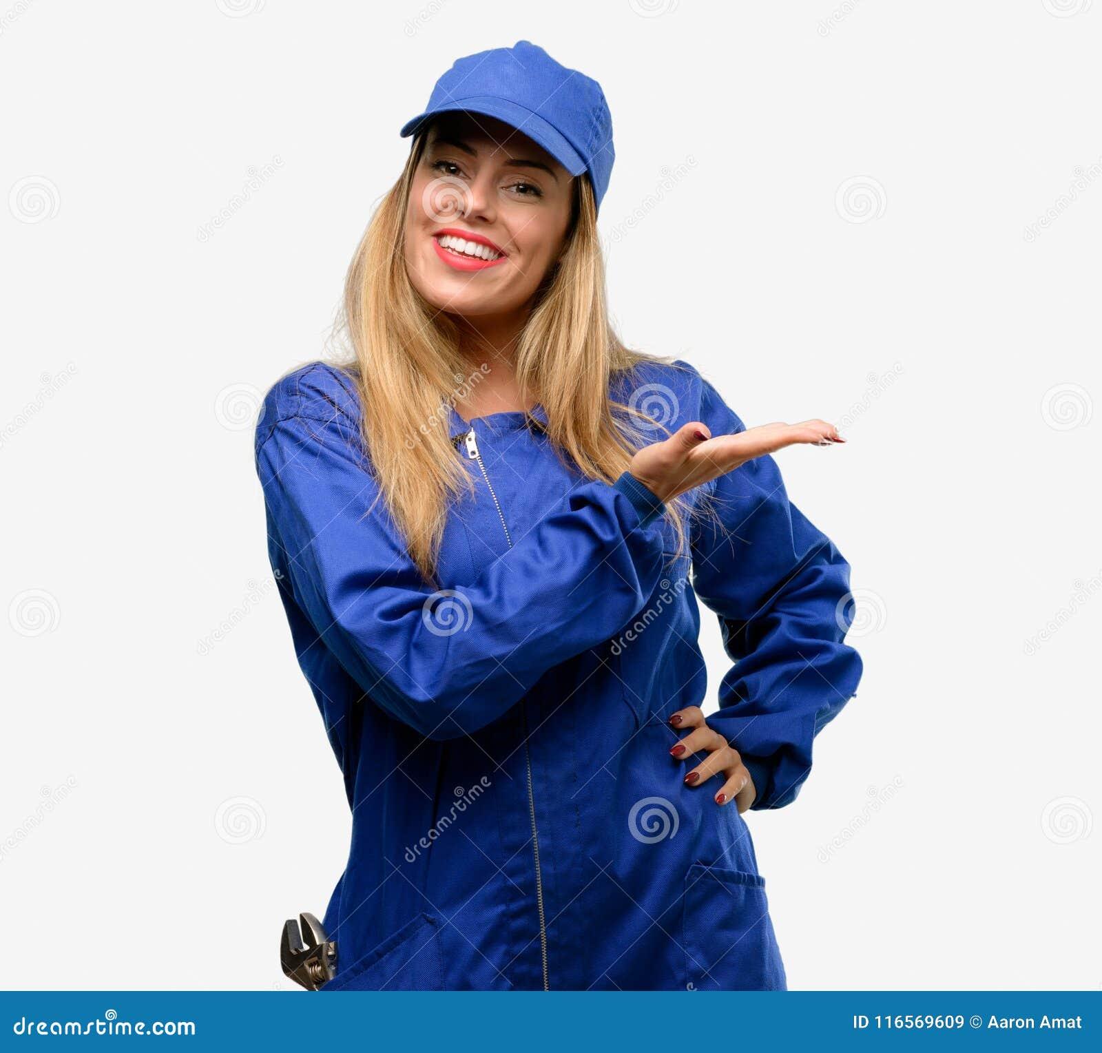 Jonge die vrouw met loodgieterkleren over grijze achtergrond wordt geïsoleerd