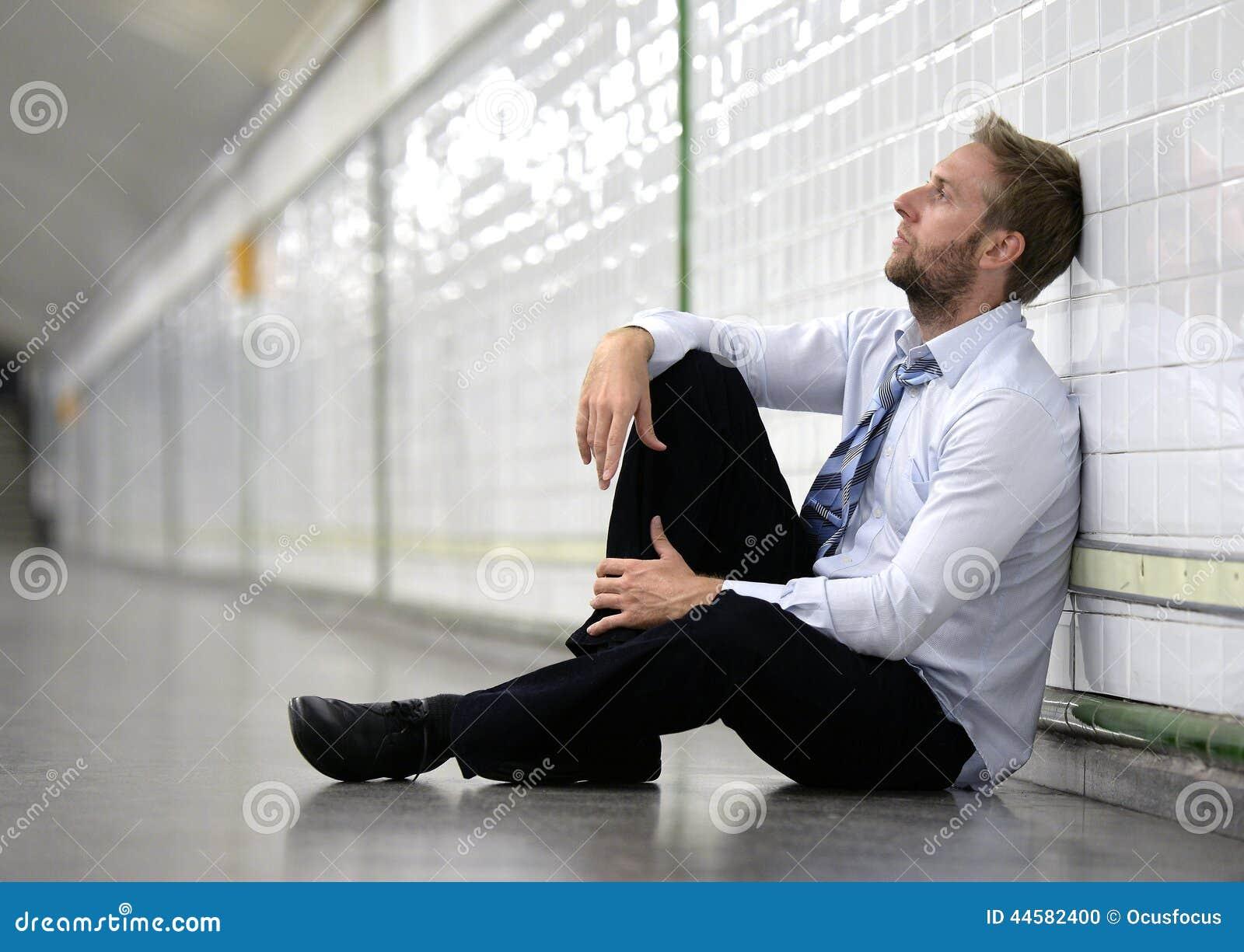 Jonge die zakenman in depressiezitting wordt verloren op de metro van de grondstraat