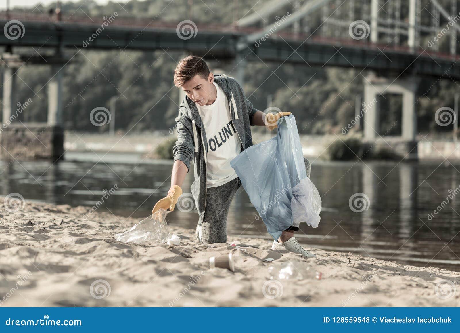 Jonge donker-haired vrijwilliger die zijn dag doorbrengen die het zand schoonmaken aan het strand