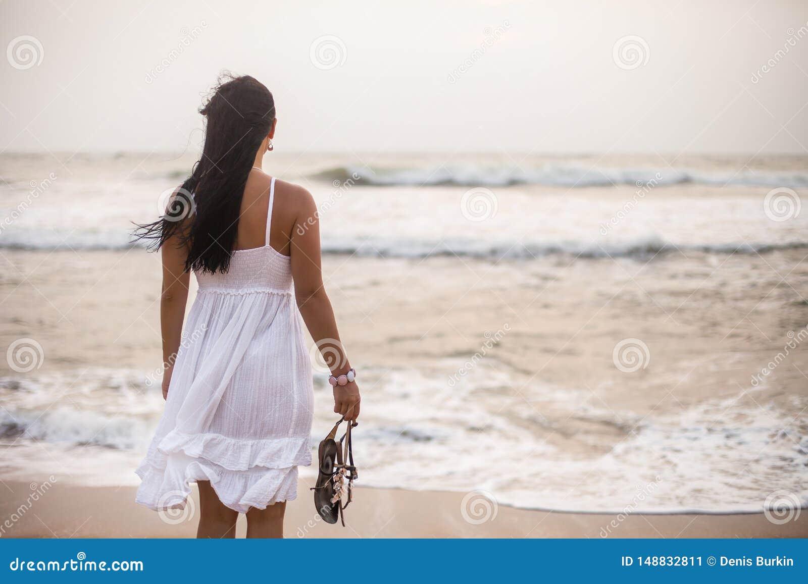 Jonge donkerbruine vrouw in de zomer witte kleding die zich op strand bevinden en aan het overzees kijken meisje het ontspannen o