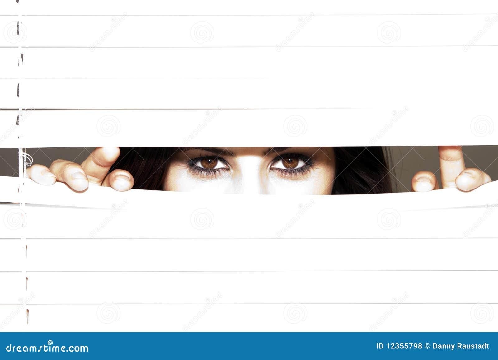 Jonge Donkerbruine Vrouw die door de Zonneblinden kijkt