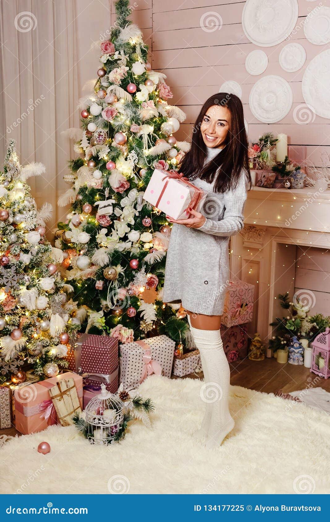 Jonge donkerbruine vrouw die met de Kerstmisgift dichtbij Kerstboom glimlachen