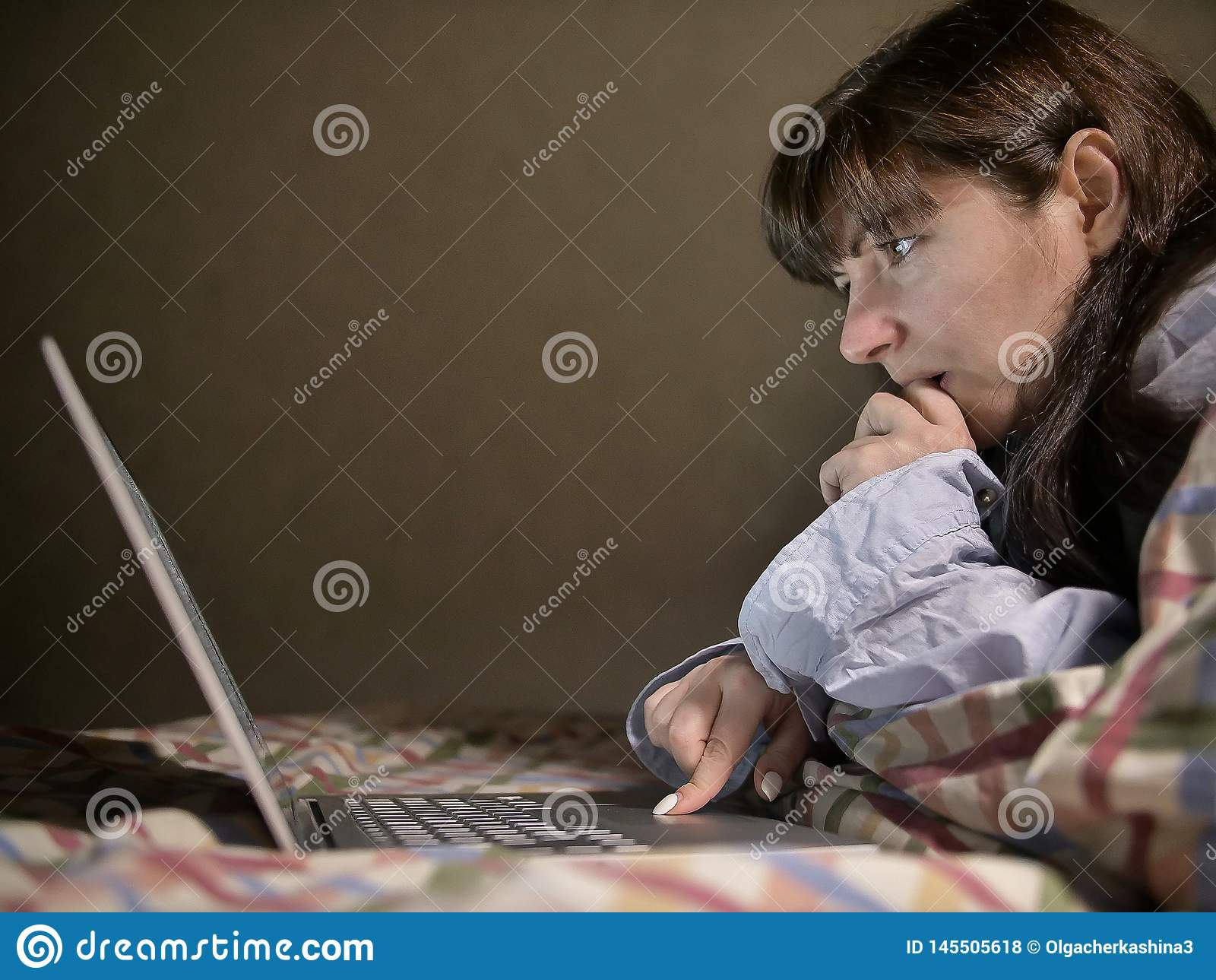 Jonge donkerbruine vrouw die op het bed liggen en in haar laptop werken