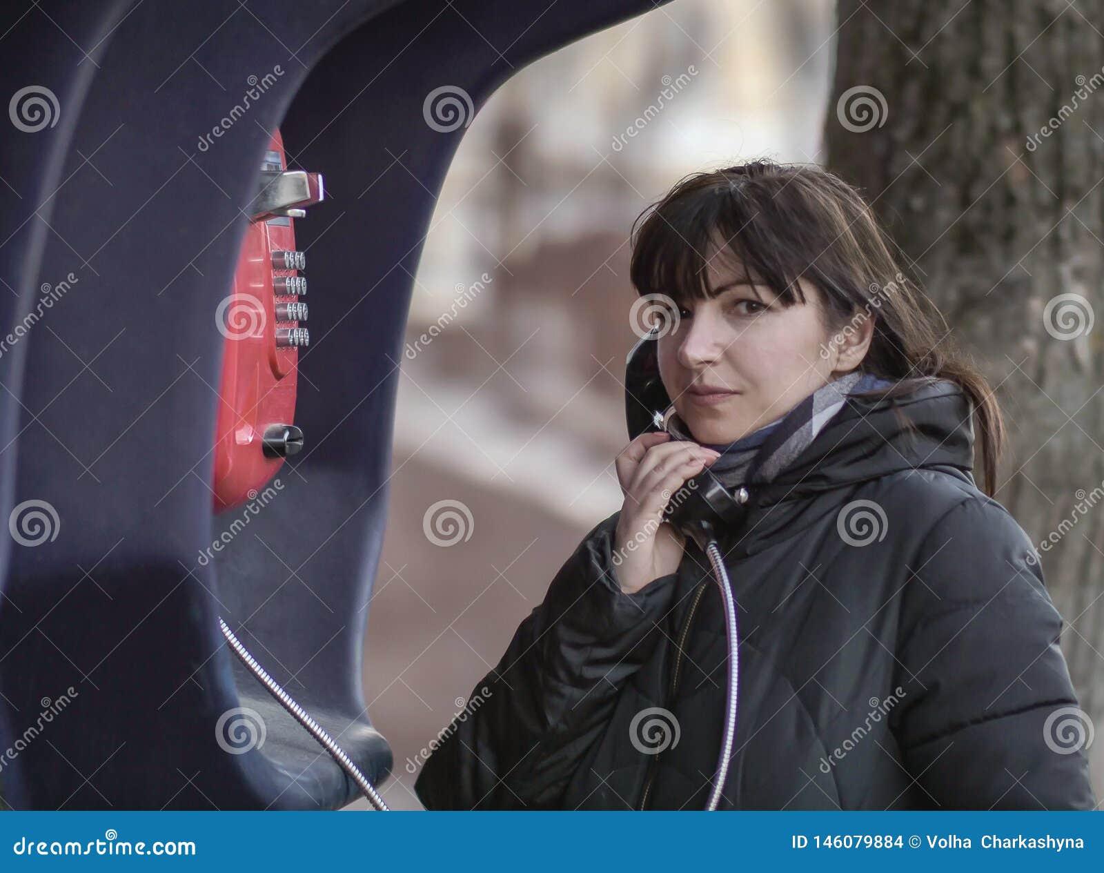 Jonge donkerbruine vrouw die van rode straatpayphone roepen, die direct de camera bekijken