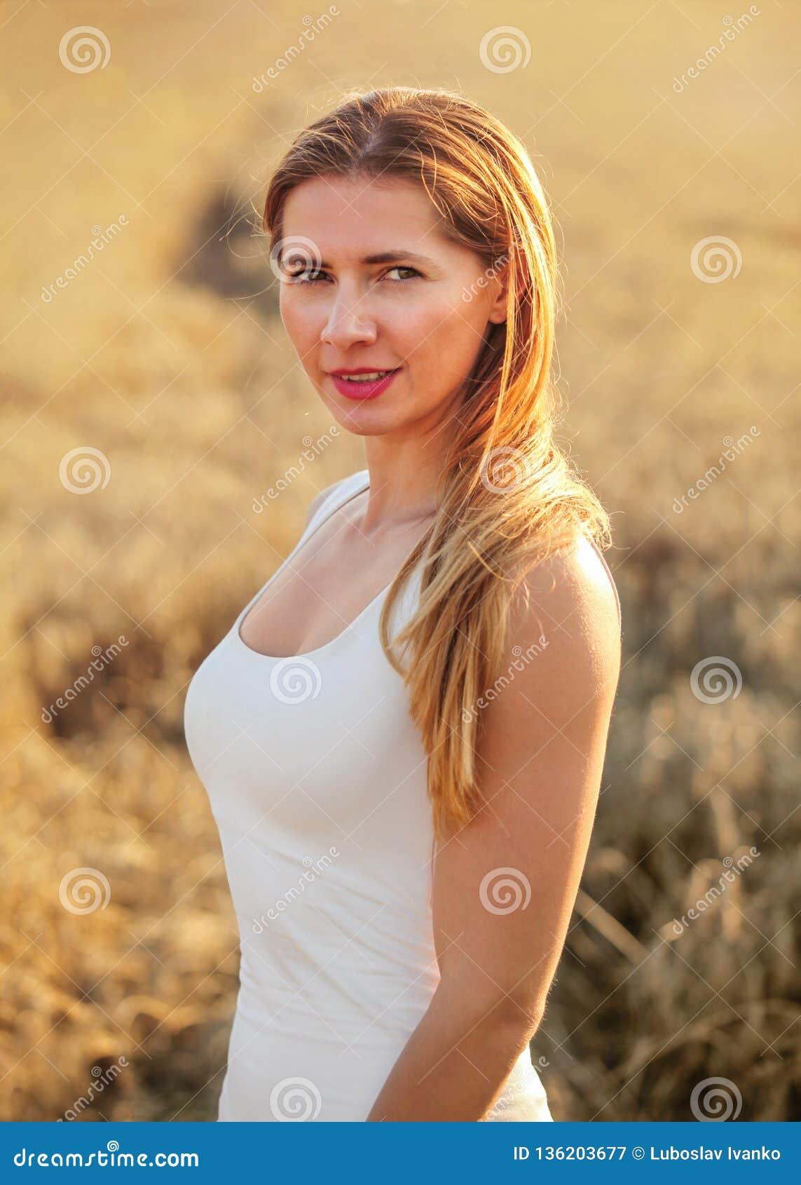 Jonge donkerbruine vrouw in witte kleding, die zich op die tarwegebied bevinden door middagzon wordt aangestoken