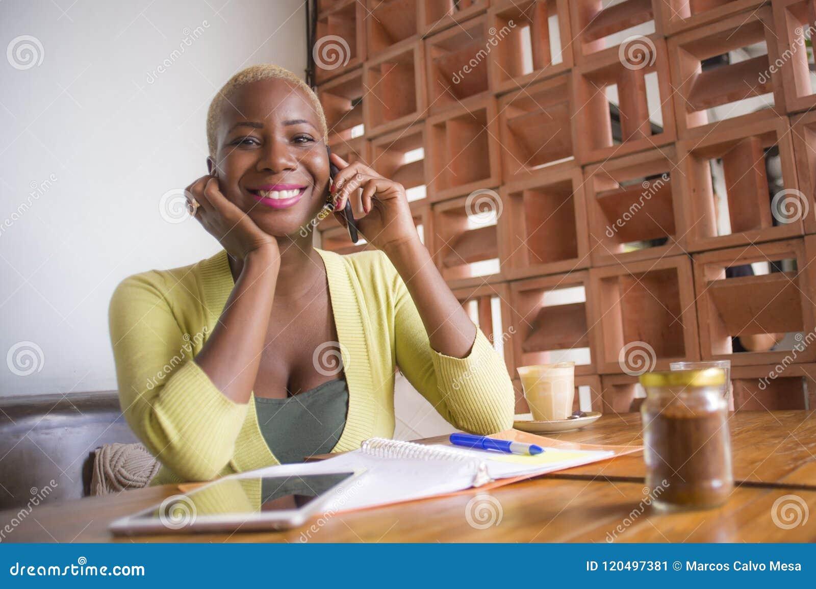 Jonge elegante en mooie zwarte Afrikaanse Amerikaanse bedrijfsvrouw die online met mobiele telefoon bij koffiewinkel gelukkig gli