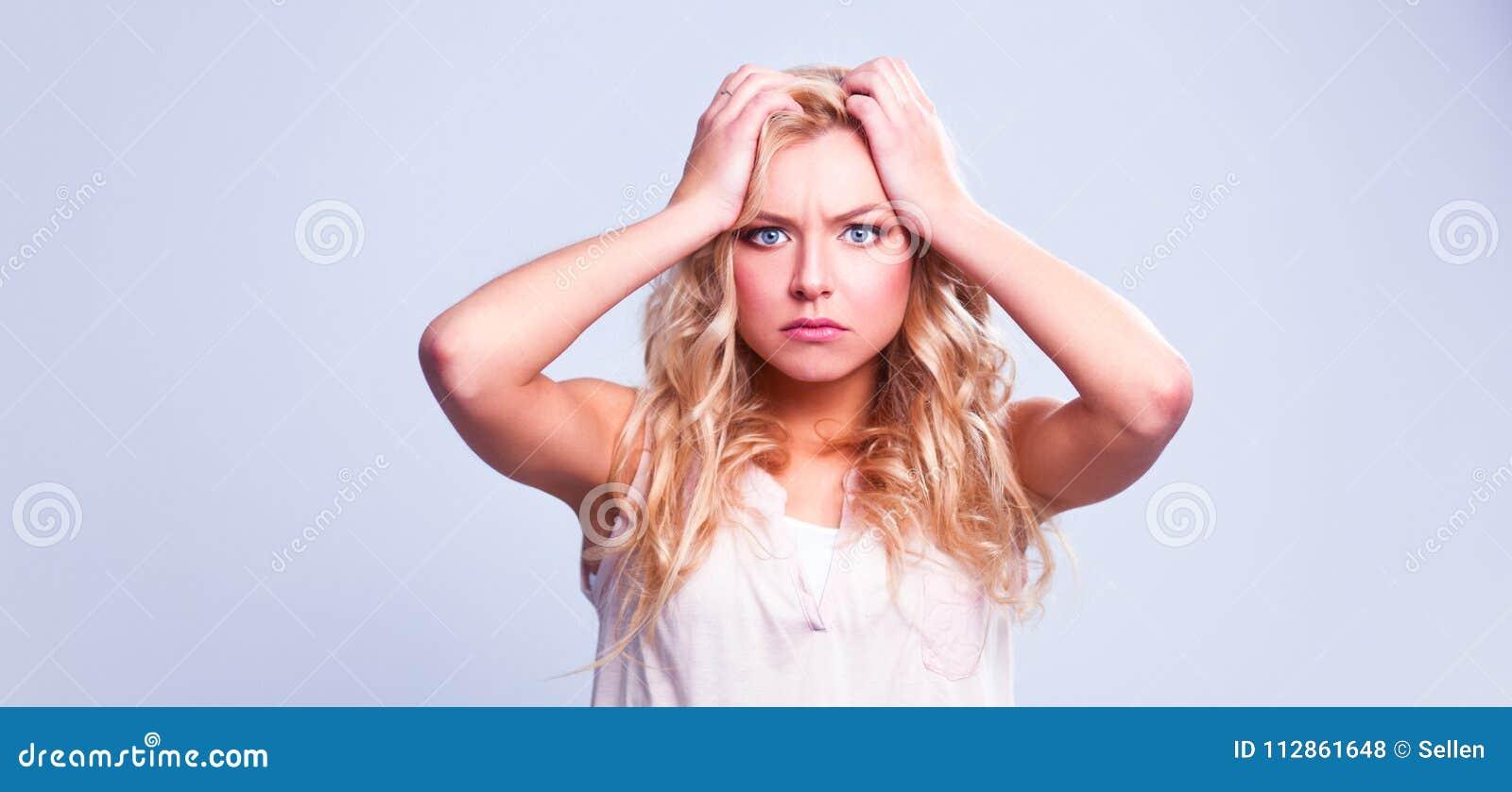 Jonge emotionele die vrouw, op grijze achtergrond wordt geïsoleerd