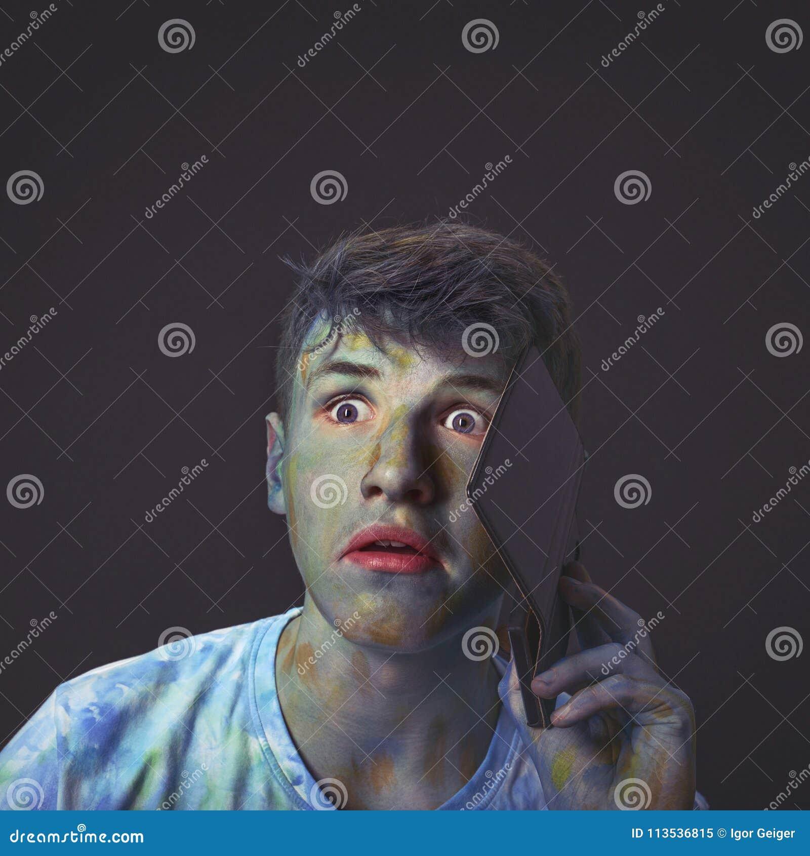 Jonge en interessante die kerel in multicolored kleuren wordt gehuld talkin
