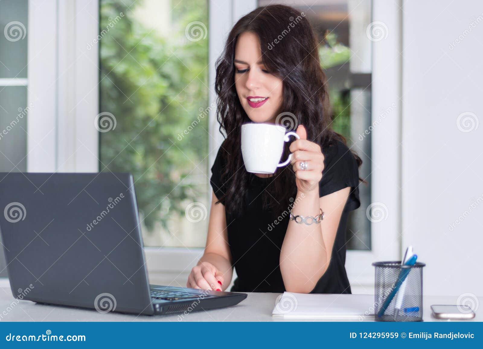 Jonge en leuke bedrijfsvrouw die aan laptop werken en kop van koffie houden