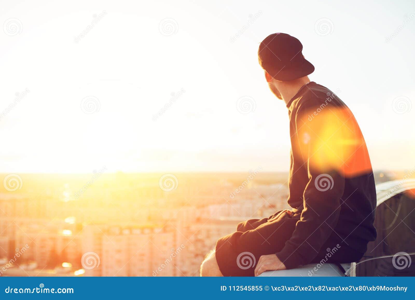 Jonge en moedige mensenzitting op de rand van het dak en het bekijken ver weg de stad