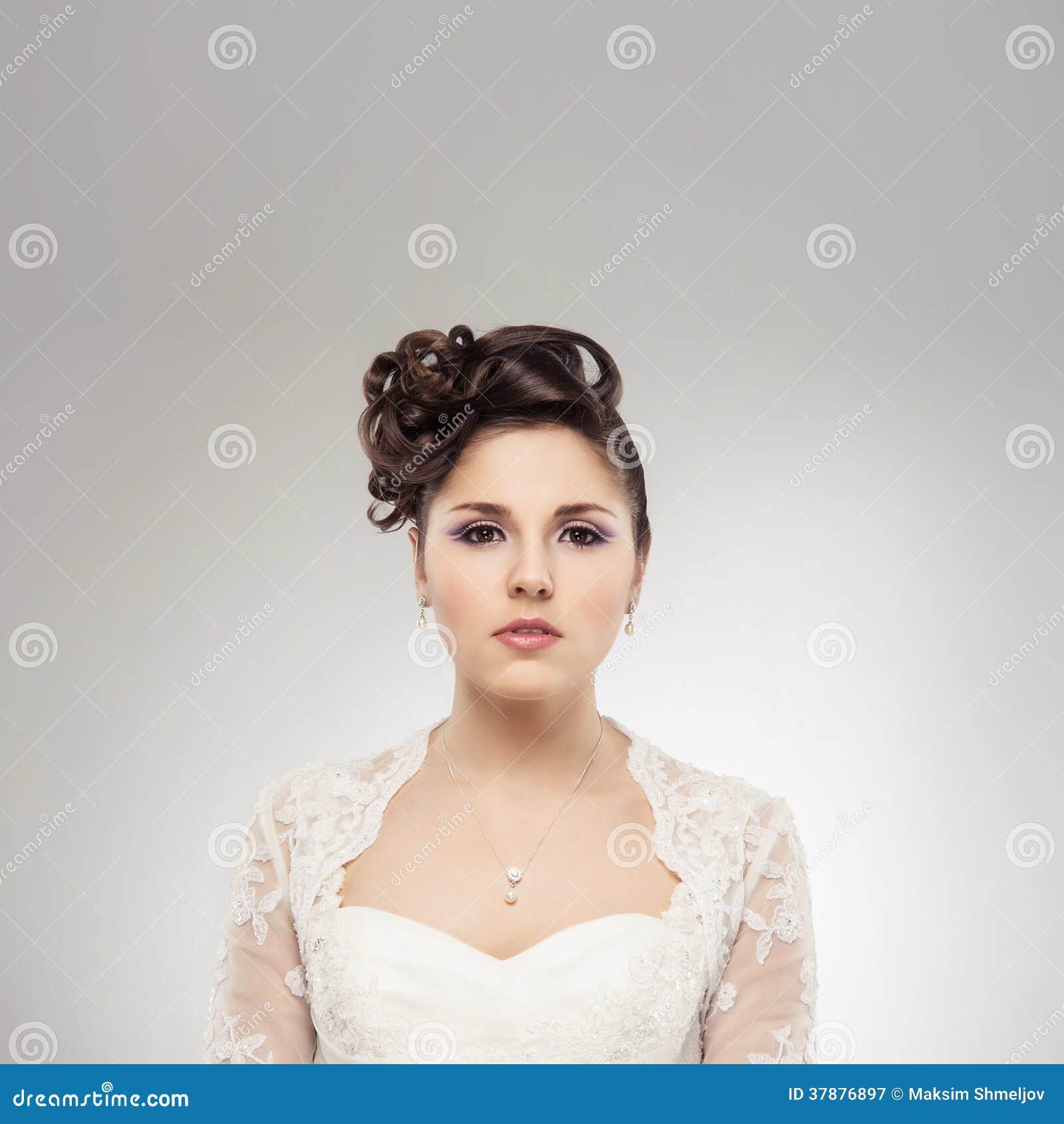 Jonge en mooie bruid over de grijze achtergrond