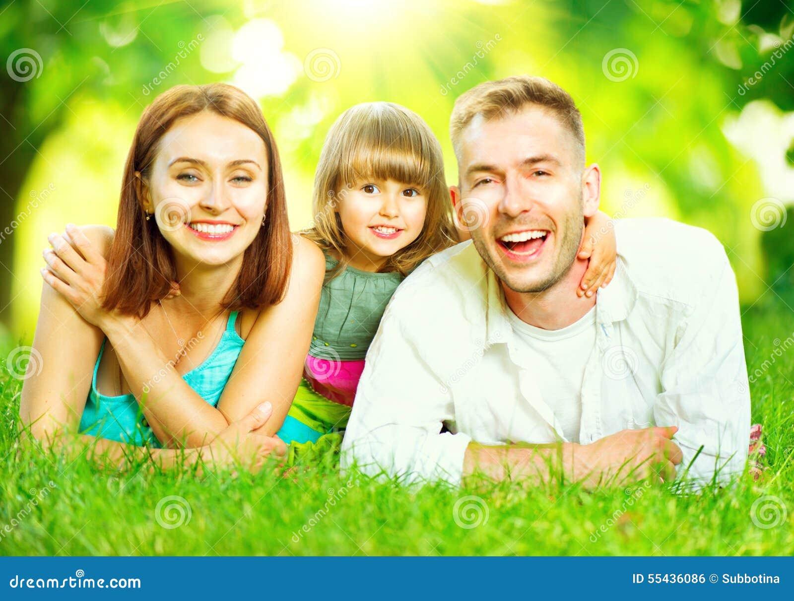Jonge familie die op groen gras liggen