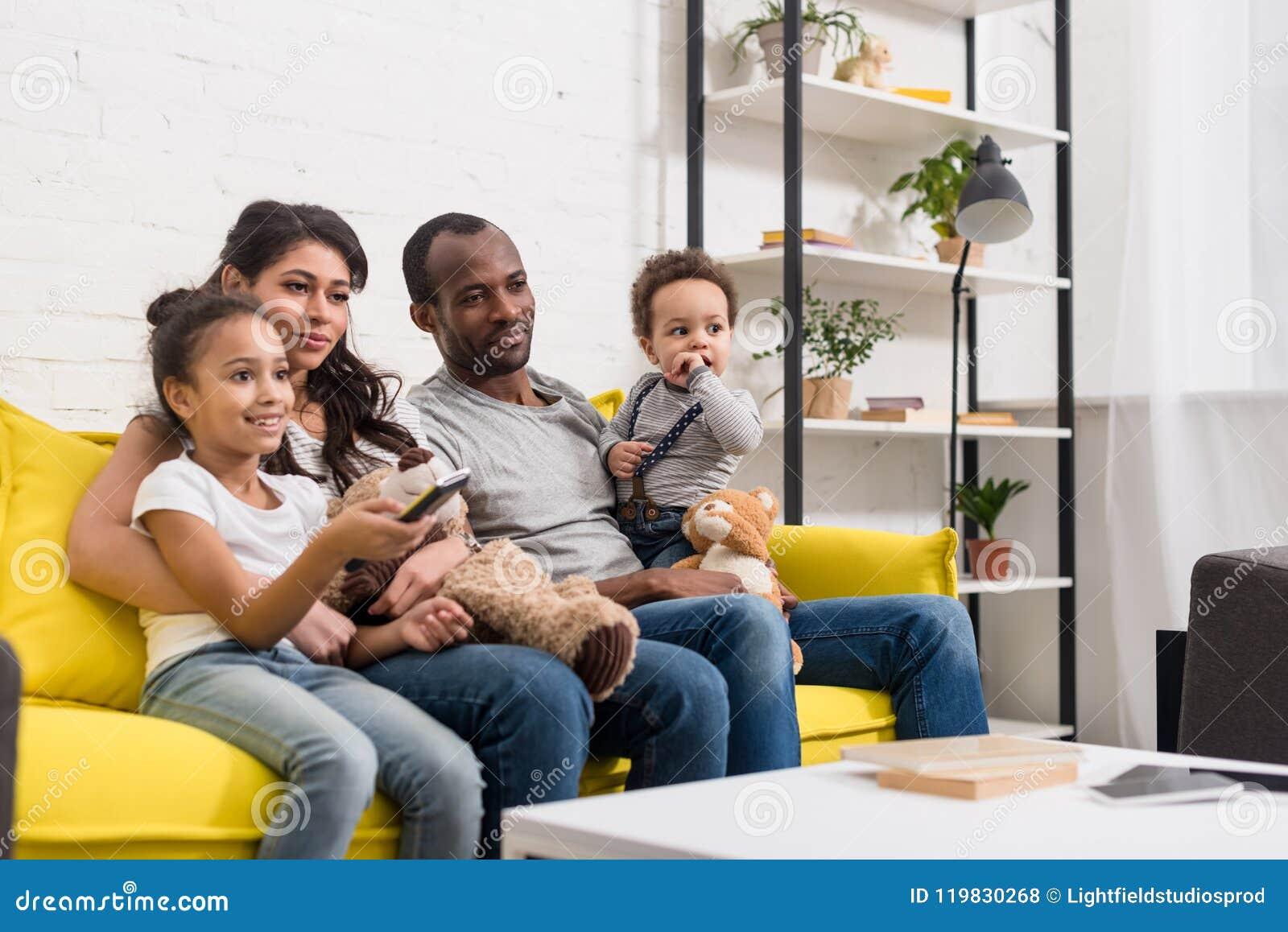 Jonge familie die op TV samen letten