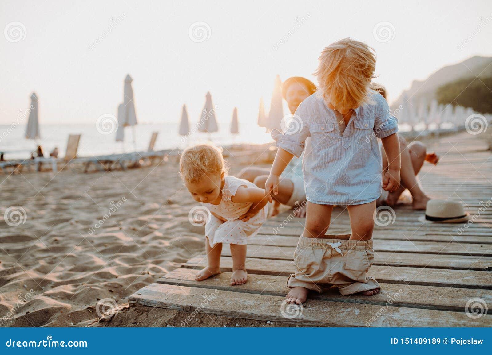 Jonge familie met peuterkinderen die pret op strand op de zomervakantie hebben