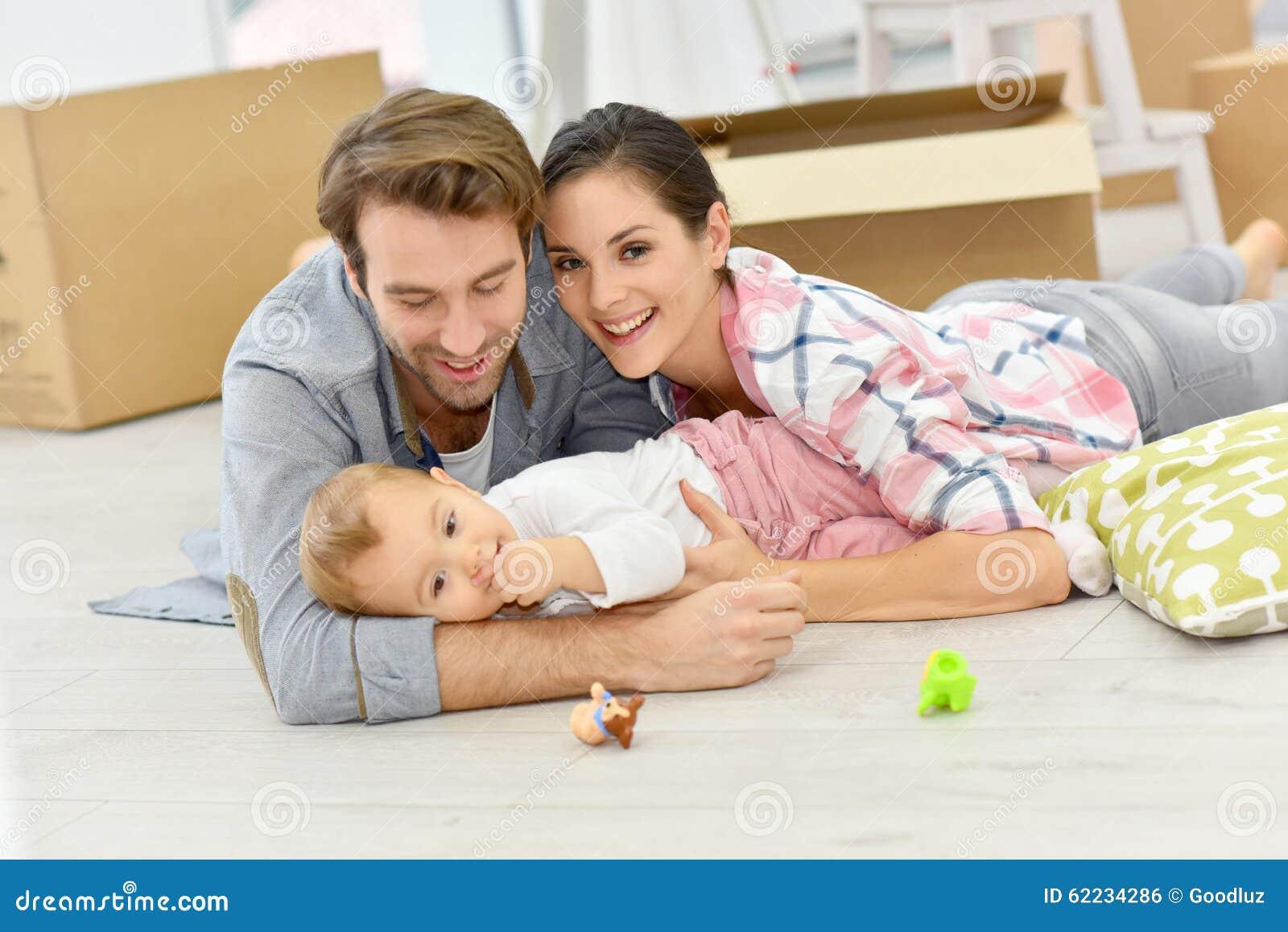 Jonge familie thuis met baby het liggen op de vloer