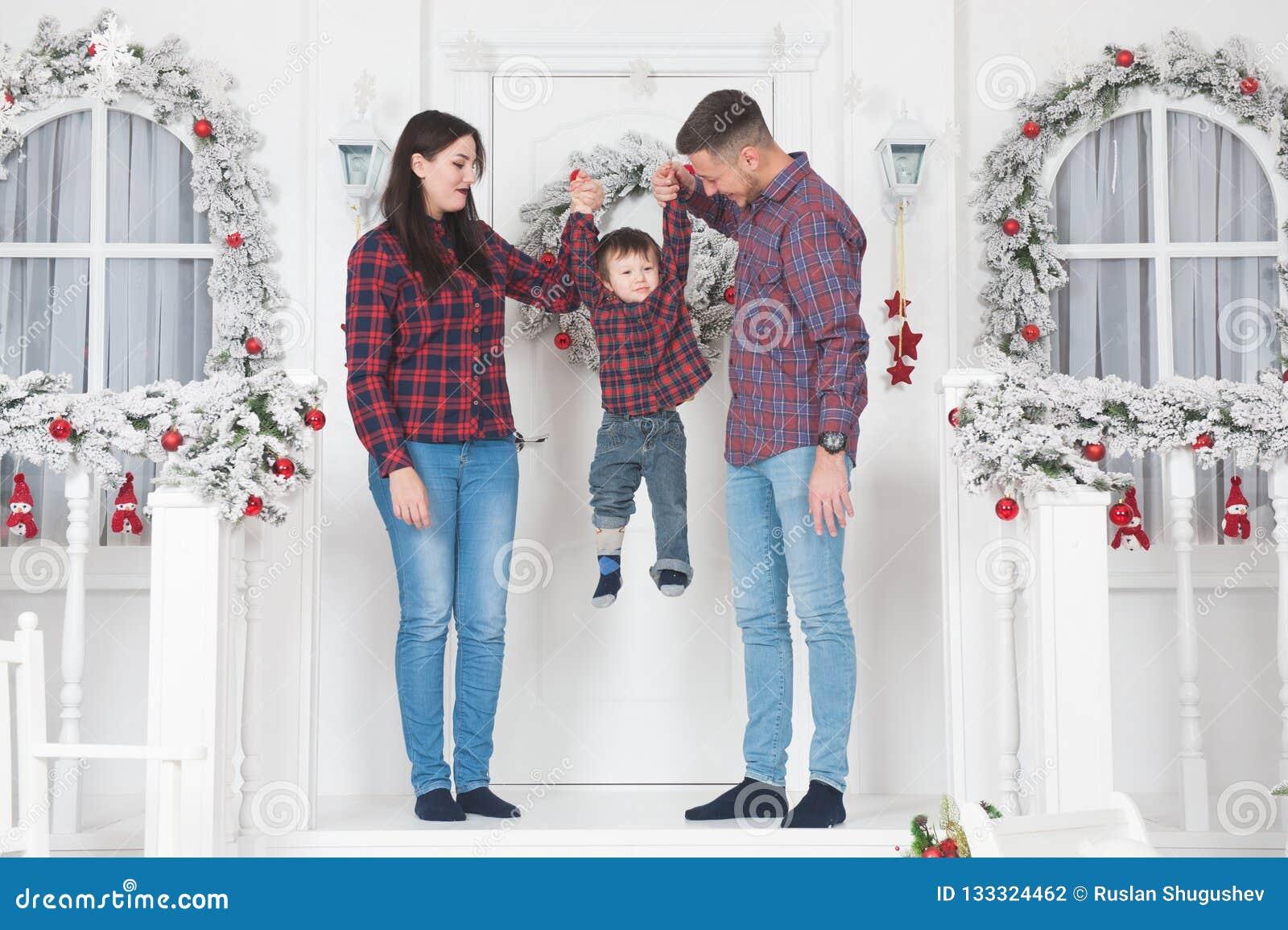 Jonge familiemamma en papa die kind opheffen die op portiek van c opstaan