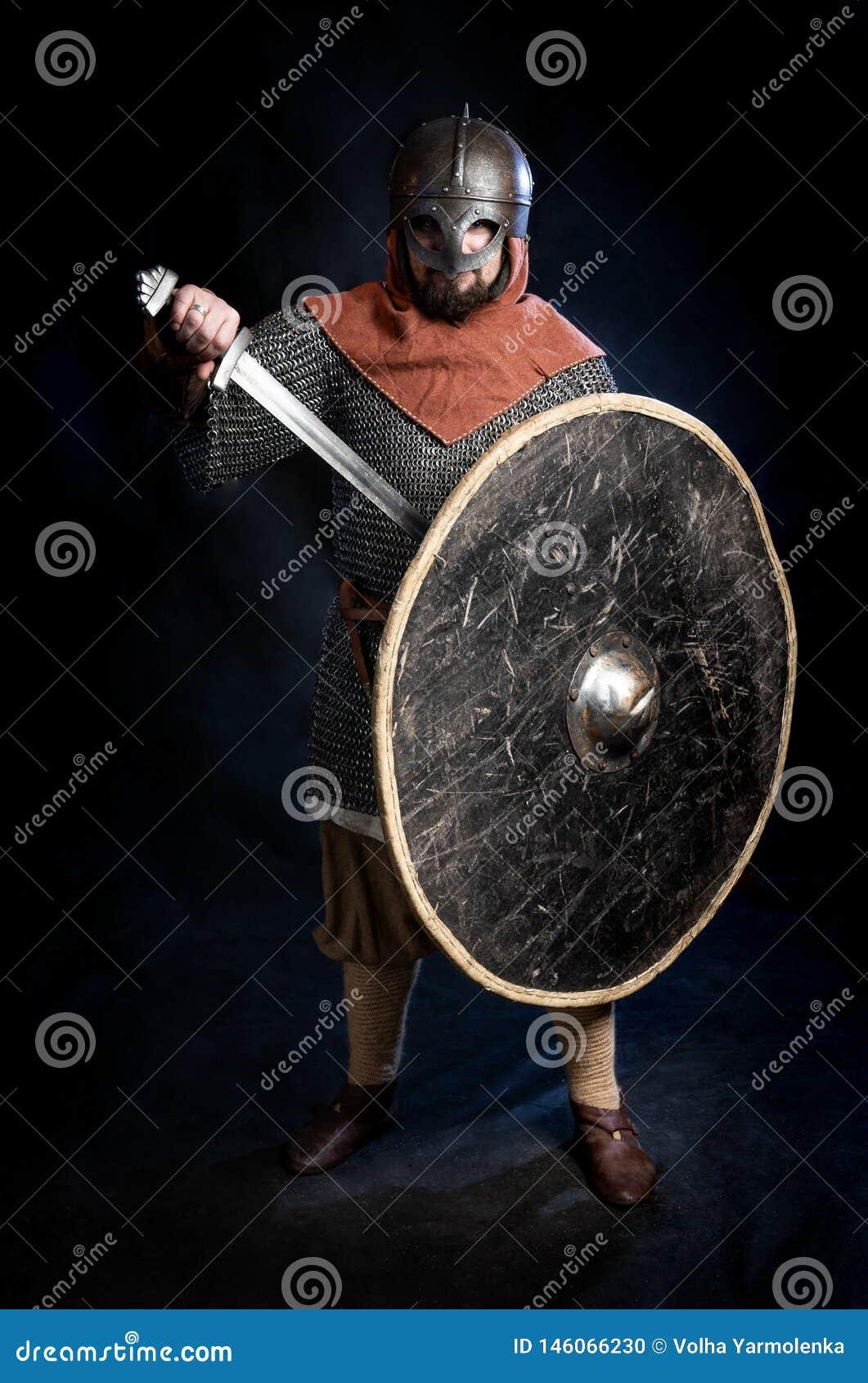 Jonge gebaarde mens in een Viking-Era helm standind en holding een zwaard en een schild