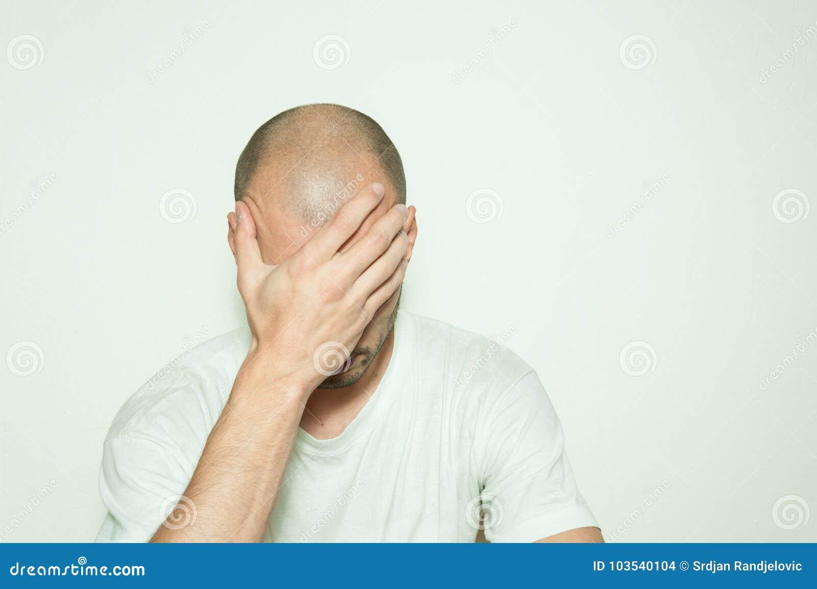 Jonge gedeprimeerde mens die aan bezorgdheid lijden en miserabele dekking voelen zijn gezicht met zijn handen en op de witte muur