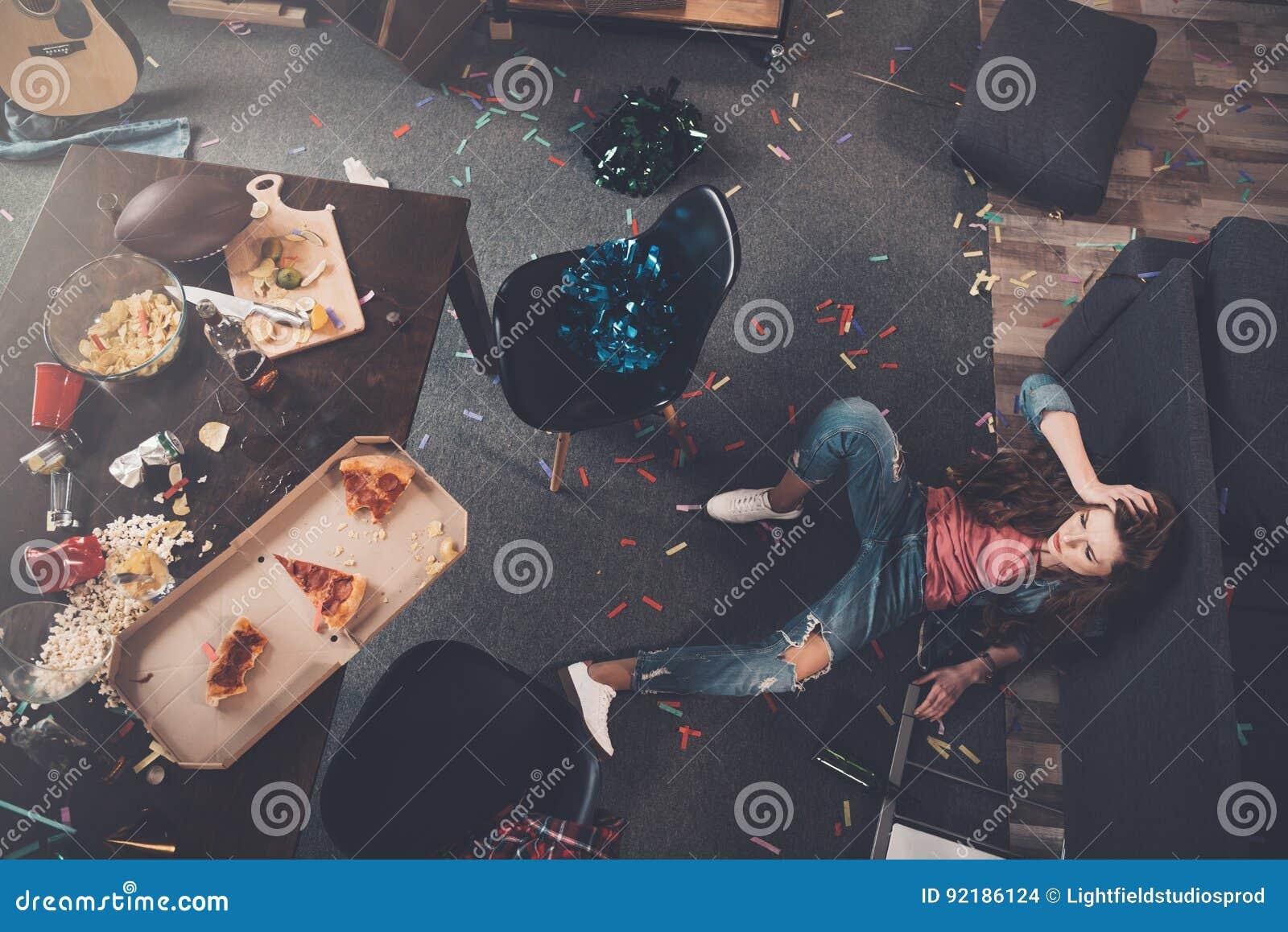 Jonge gedronken vrouw die op vloer in slordige ruimte liggen