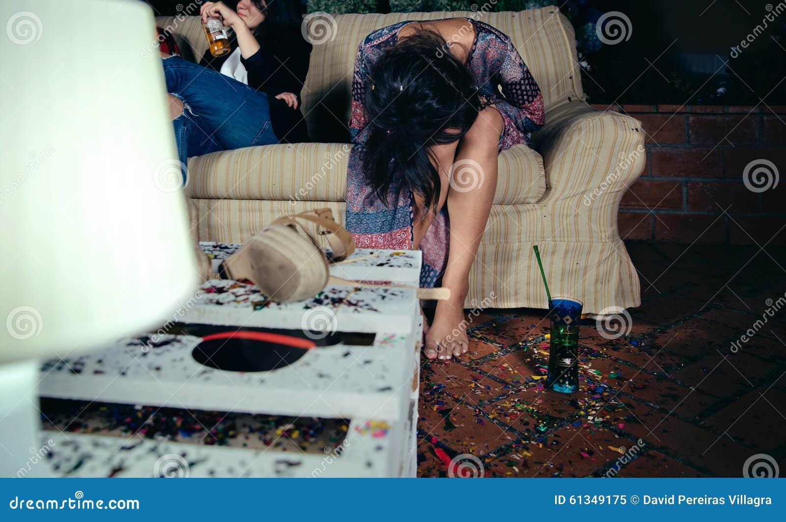 Jonge gedronken vrouwenzitting in de bank op een partij