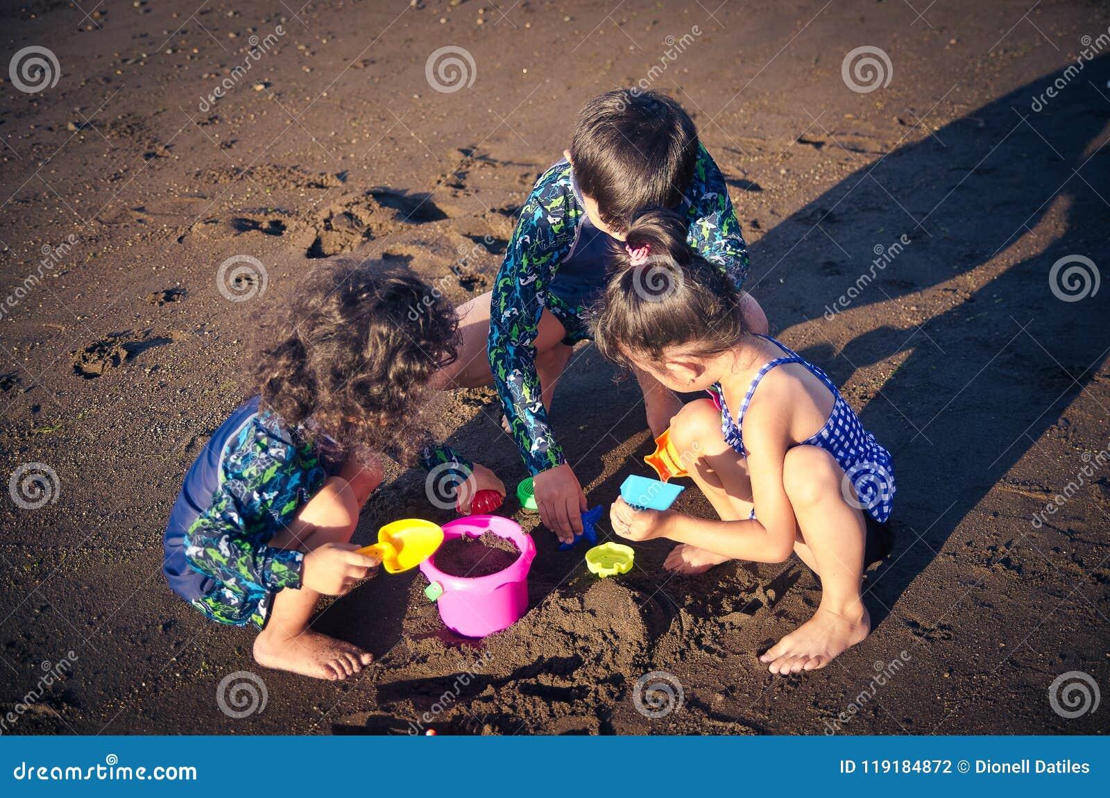 Jonge geitjes die bij het strand spelen