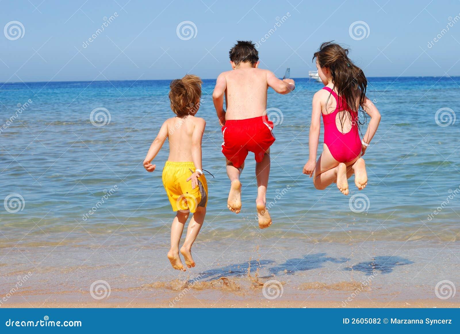 Jonge geitjes die bij het strand springen